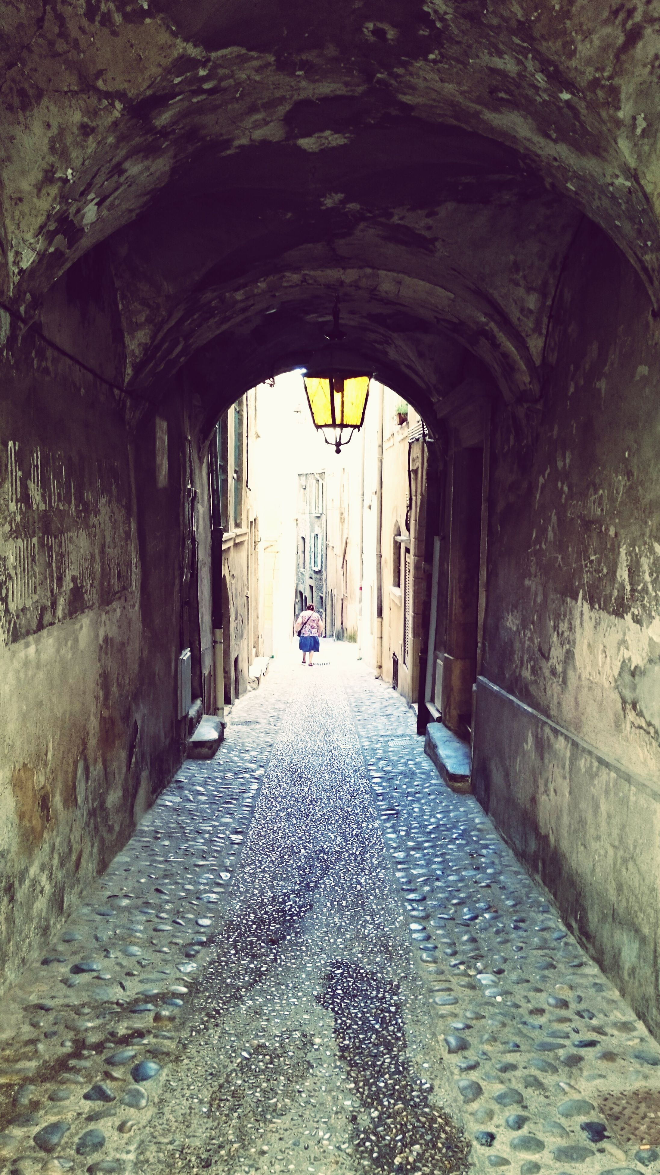 arch, architecture, built structure, the way forward, incidental people, building exterior, cobblestone, archway, day, diminishing perspective, the past, history, narrow, outdoors, alley, leading, old town, stone material, footpath, long, pedestrian walkway