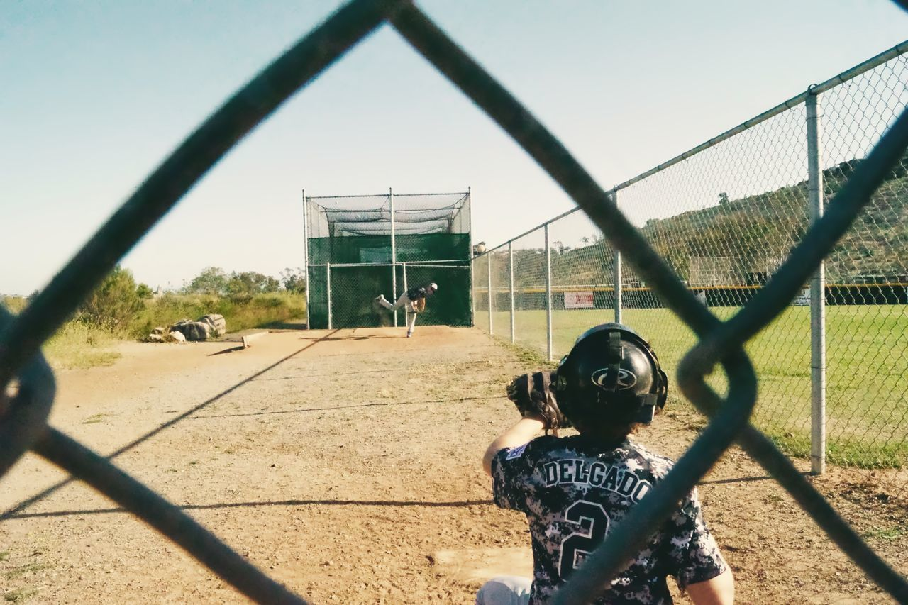 Baseball - Sport Baseball Bat Baseball Helmet Baseball Player Batting Boys Chainlink Fence Childhood Competition Day Headwear Helmet Leisure Activity Lifestyles One Person Outdoors People Playing Playing Field Real People Rear View Sport Standing