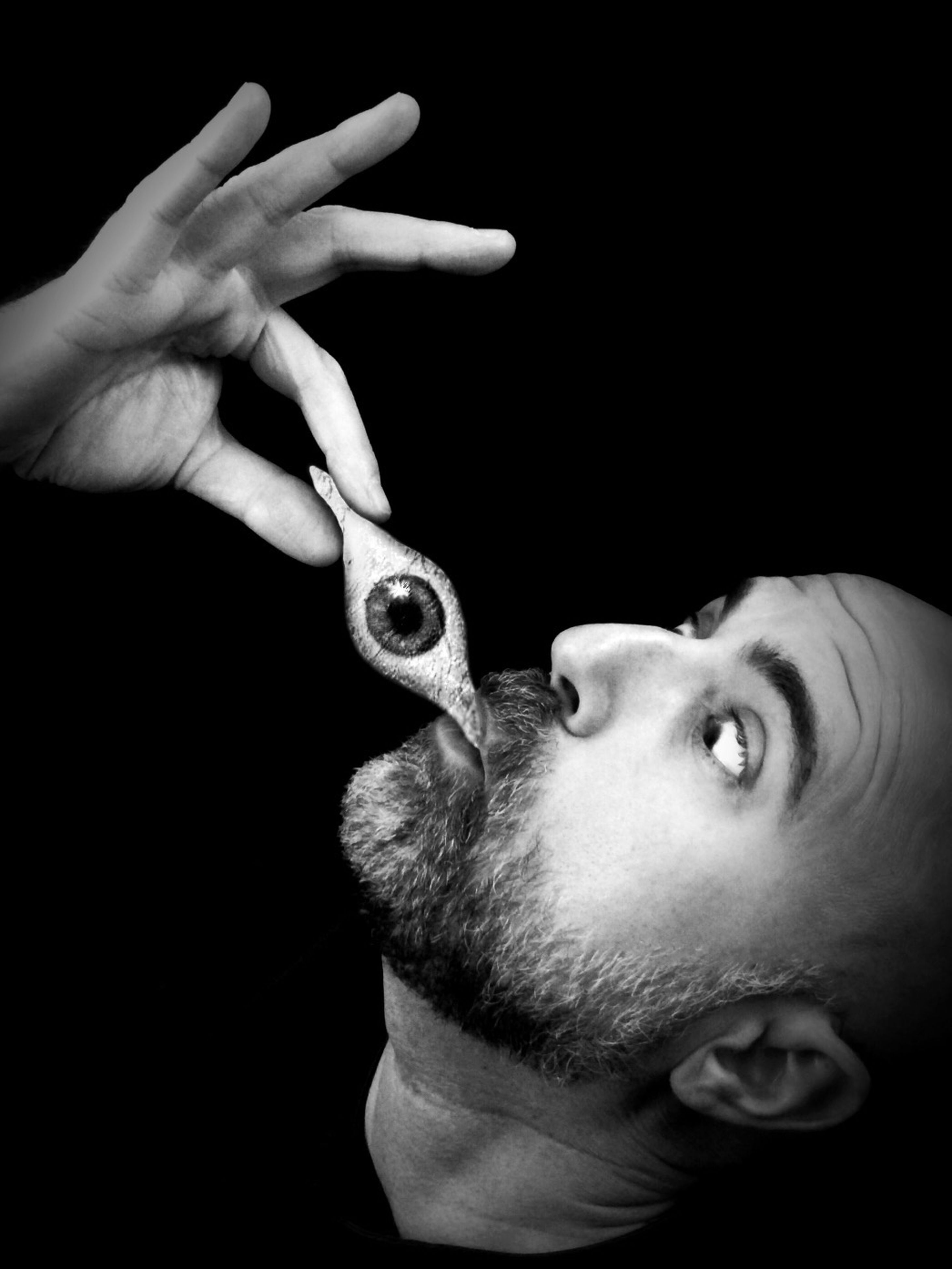 person, black background, studio shot, indoors, holding, part of, human finger, close-up, lifestyles, cropped, leisure activity, men, copy space, unrecognizable person, front view, headshot