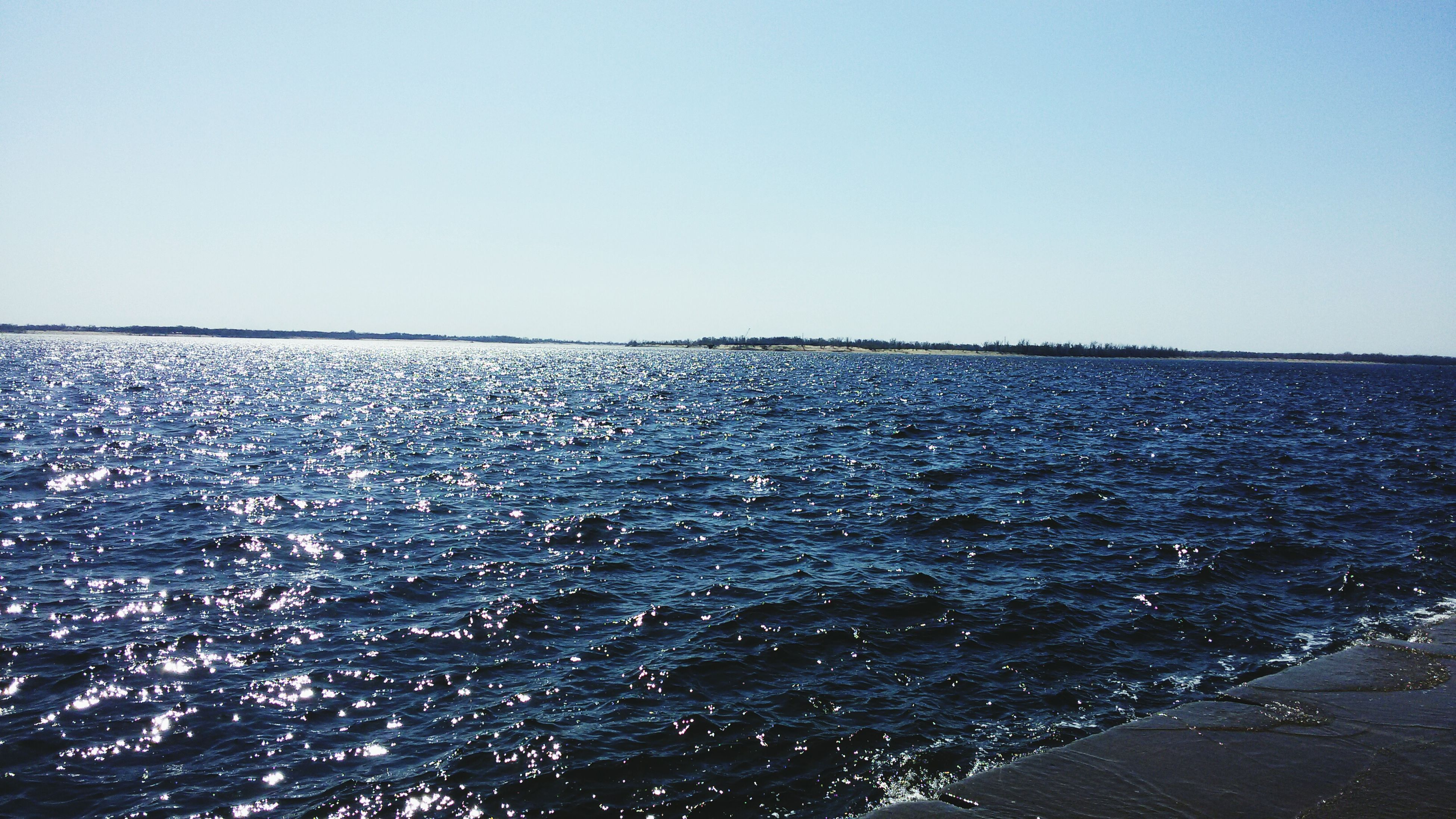 water, clear sky, copy space, sea, tranquil scene, tranquility, scenics, beauty in nature, rippled, waterfront, nature, blue, horizon over water, idyllic, day, outdoors, no people, remote, seascape, sky