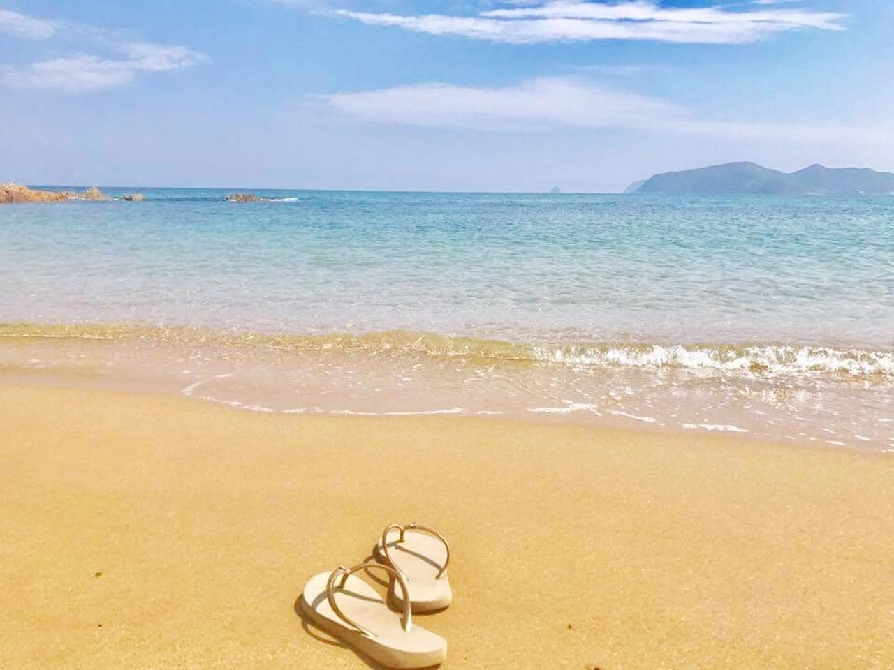 sea, beach, pair, sand, water, shoe, beauty in nature, sandal, tranquility, no people, horizon over water, nature, scenics, day, sky, outdoors, wave