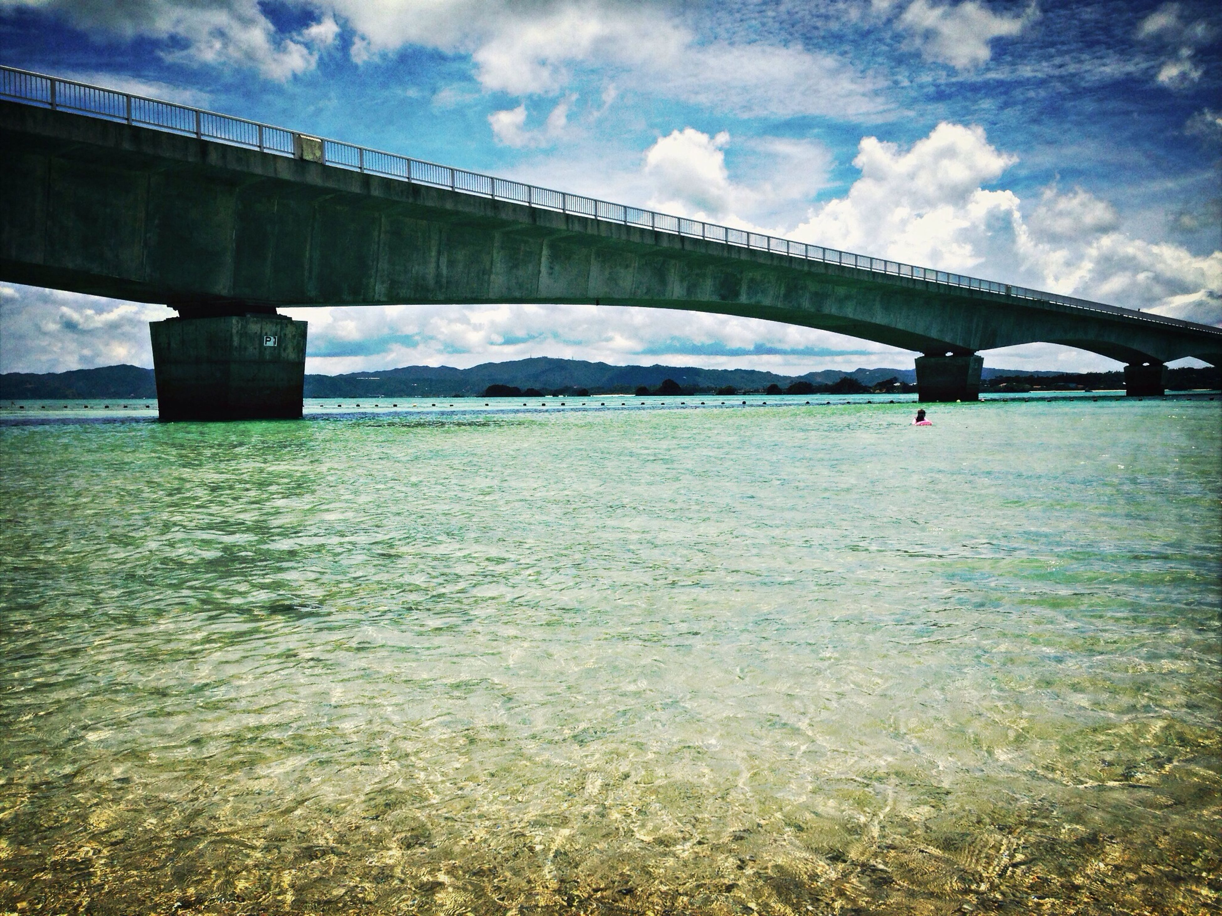 bridge - man made structure, connection, transportation, water, sky, river, engineering, cloud - sky, waterfront, bridge, built structure, architecture, mode of transport, cloud, cloudy, suspension bridge, rippled, nature, tranquility, travel