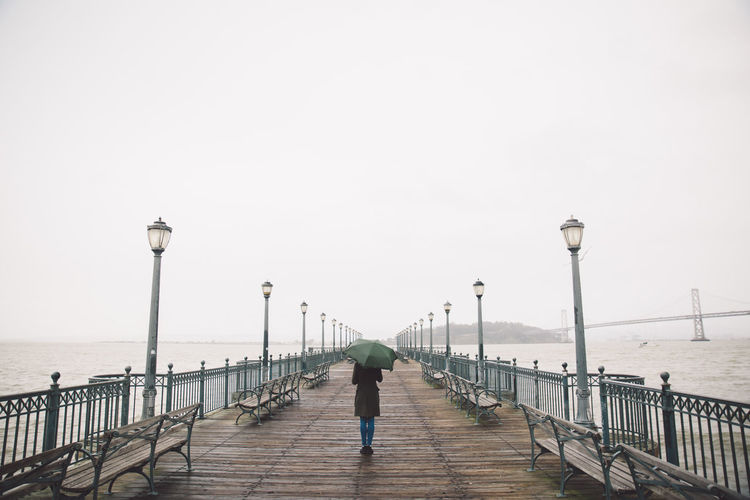 2017 Beach Bridge - Man Made Structure Built Structure Curly Hair Day February Full Length Girl Horizon Over Water Men One Person Outdoors Pier Pier Railing Real People Rear View San Francisco Sea Sky Street Light Umbrella Walking Water