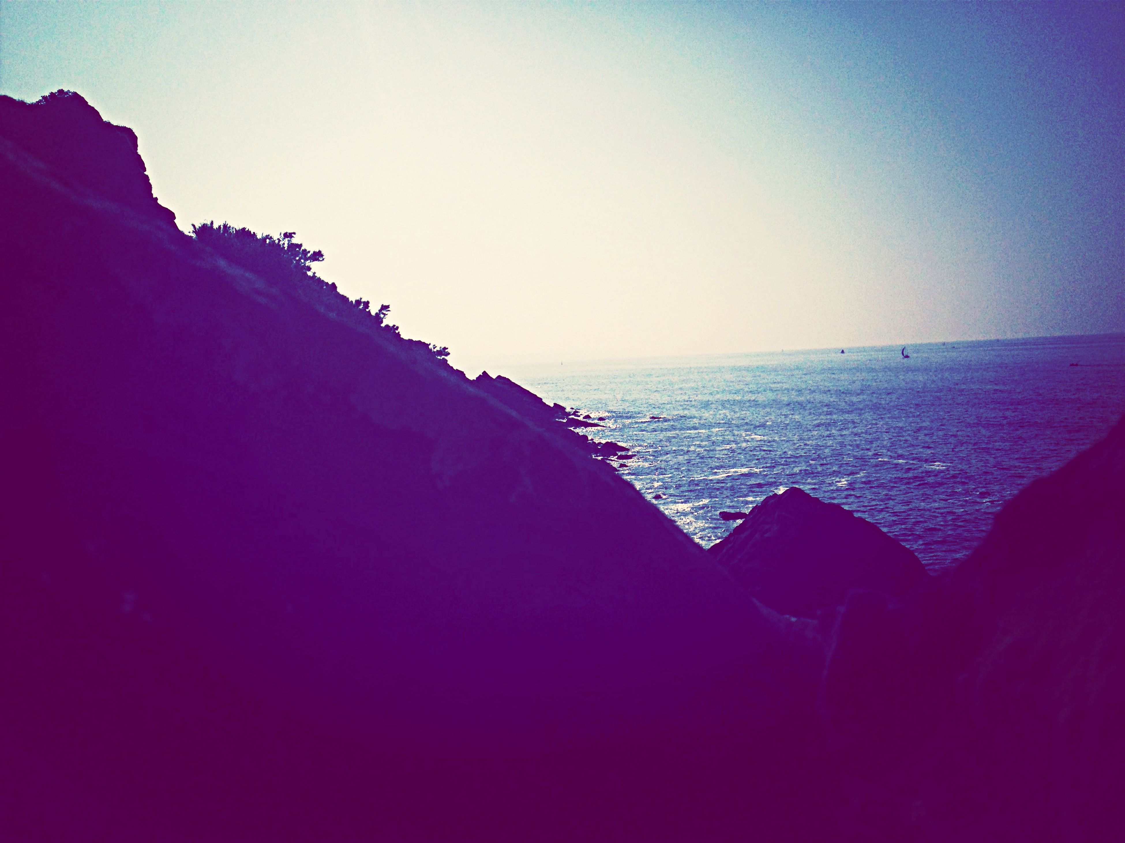 sea, horizon over water, clear sky, copy space, water, scenics, tranquil scene, beauty in nature, tranquility, nature, beach, idyllic, blue, remote, shore, non-urban scene, seascape, outdoors, calm, rock formation
