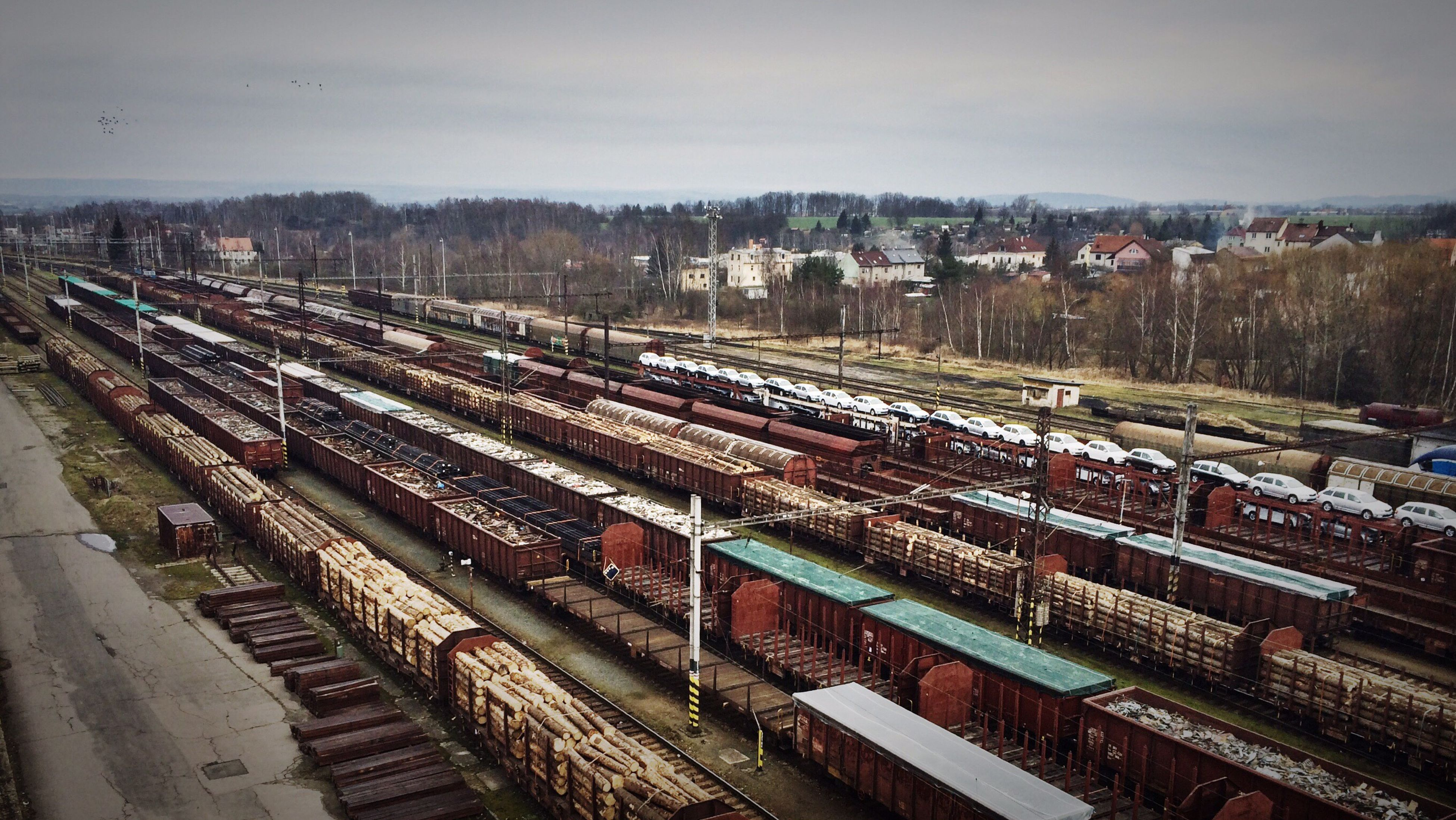 transportation, high angle view, railroad track, built structure, public transportation, sky, rail transportation, building exterior, city, architecture, mode of transport, road, outdoors, railroad station, street, diminishing perspective, car, railroad station platform, day, no people