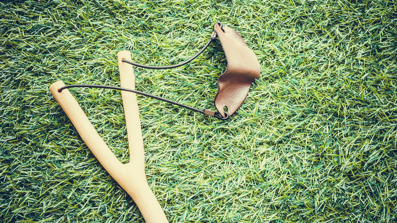 Retro styled or retro color slingshot on wooden grass. Aim Catapult Childhood Childhood Memories Day Game Grass Green Color Slingshot Wood