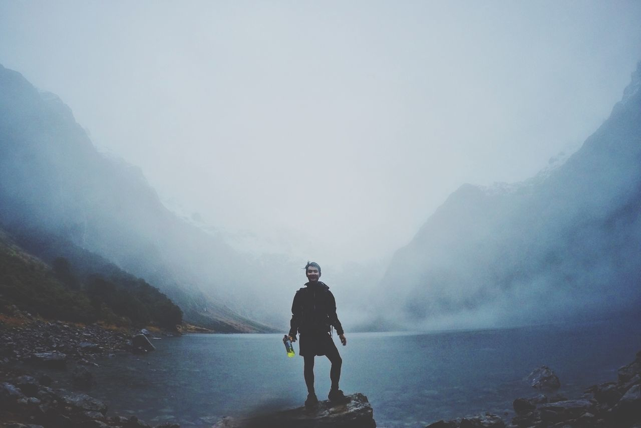 fog, real people, nature, mountain, beauty in nature, foggy, leisure activity, one person, lifestyles, full length, outdoors, water, scenics, day, tranquil scene, standing, vacations, young adult, tranquility, adventure, landscape, winter, men, sky, young women, people
