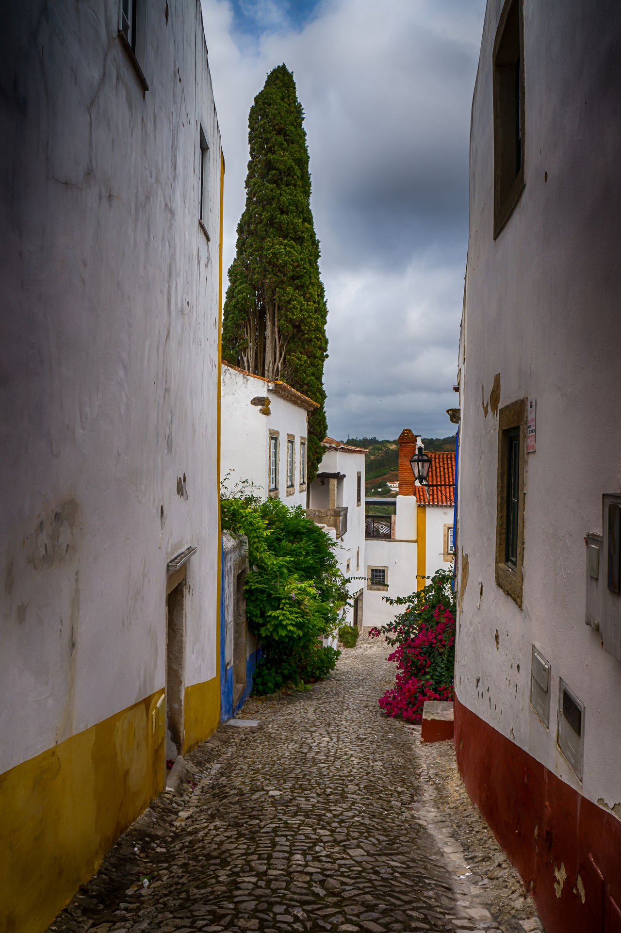 """Óbidos is a Portuguese town in the district of Leiria, in the Centre Portuguese region and close to the Atlantic Ocean coast. The name Óbidos comes from the Latin """"oppidum"""", which means """"fortified city"""". Definitely a """"must see destination"""" on your next trip to this surprising country. Find more here http://bit.ly/1NjgnA5 Beautiful Building Exterior Cities City Discovering Europe Exterior Leiria Medieval Narrow Photography Places Portugal Street Town Travel Traveling Visiting Óbidos"""