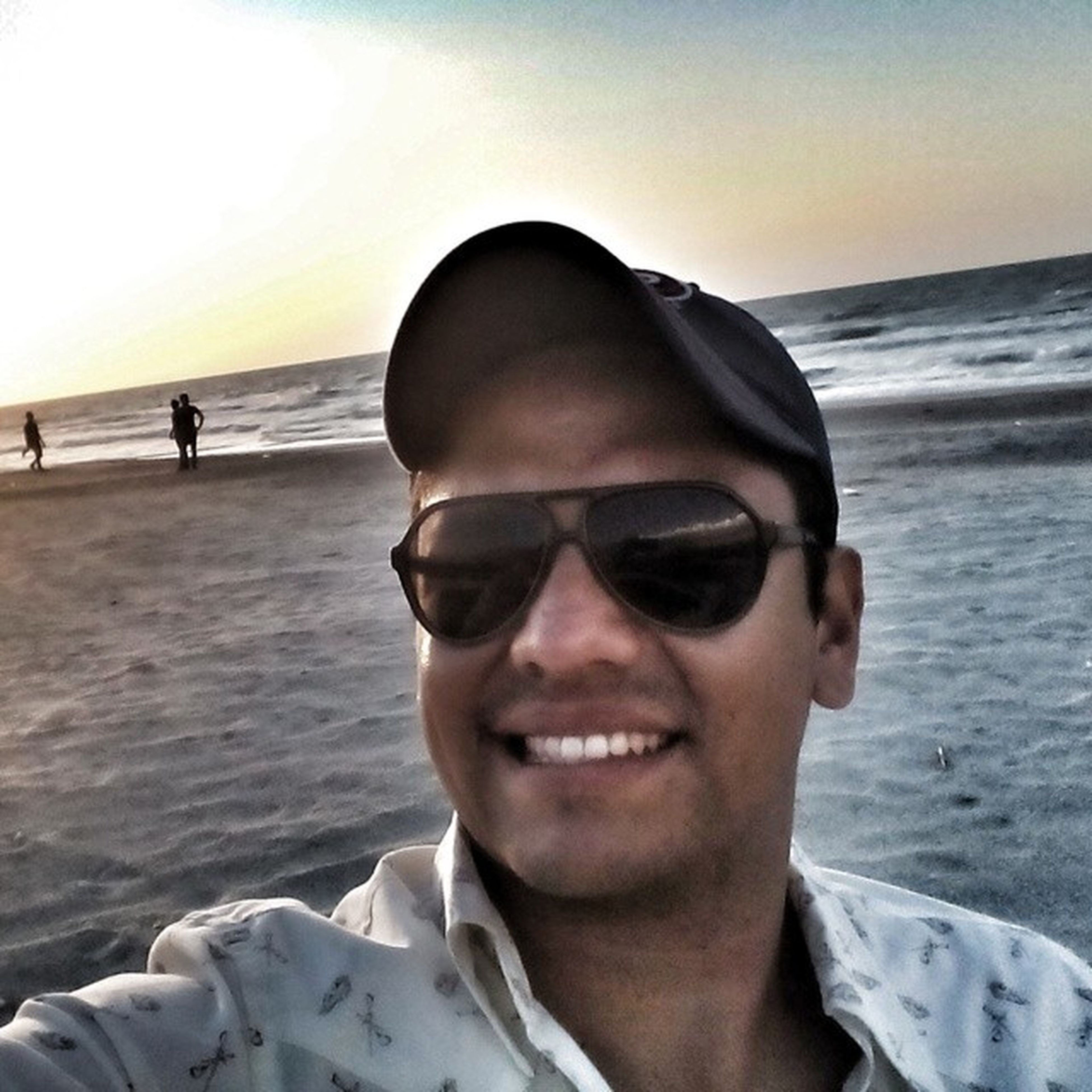 sunglasses, beach, sea, lifestyles, portrait, young adult, person, leisure activity, young men, headshot, looking at camera, water, vacations, shore, front view, head and shoulders, sand, sky