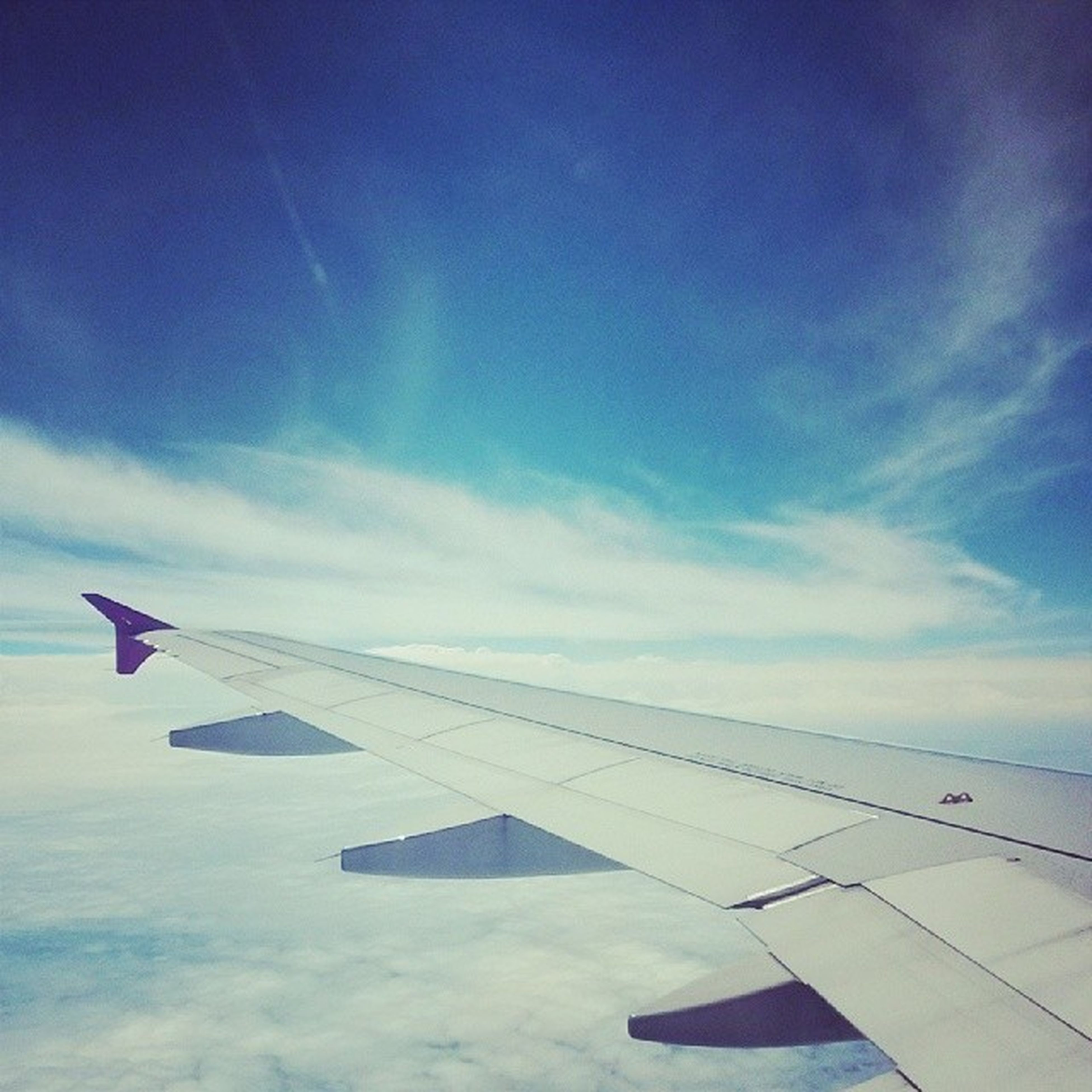 flying, airplane, air vehicle, aircraft wing, transportation, mode of transport, mid-air, sky, part of, blue, cropped, travel, cloud - sky, journey, on the move, aerial view, public transportation, cloud, airplane wing, aeroplane