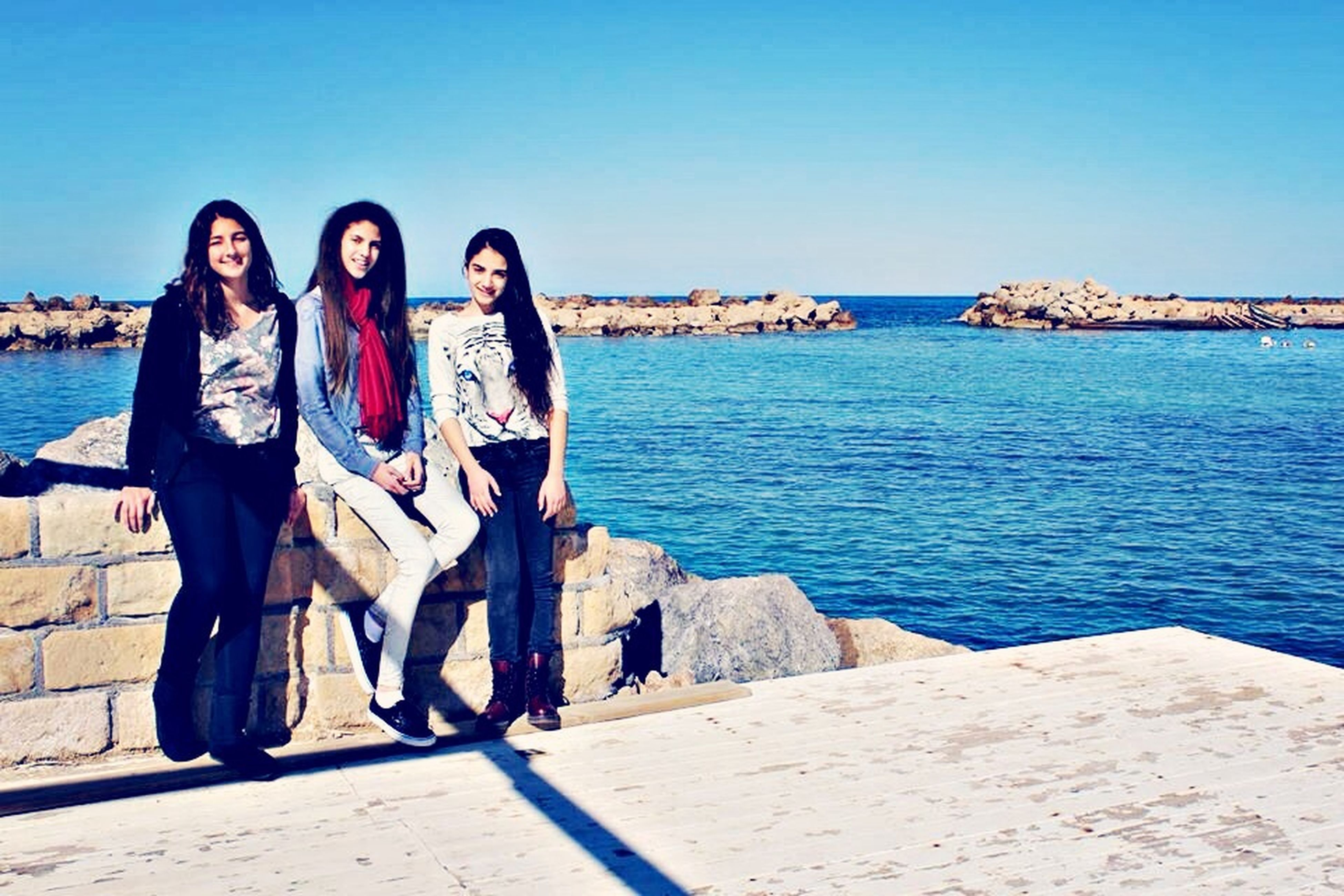 water, clear sky, lifestyles, sea, leisure activity, blue, full length, casual clothing, standing, copy space, young adult, vacations, person, togetherness, sunlight, young women, horizon over water, beach