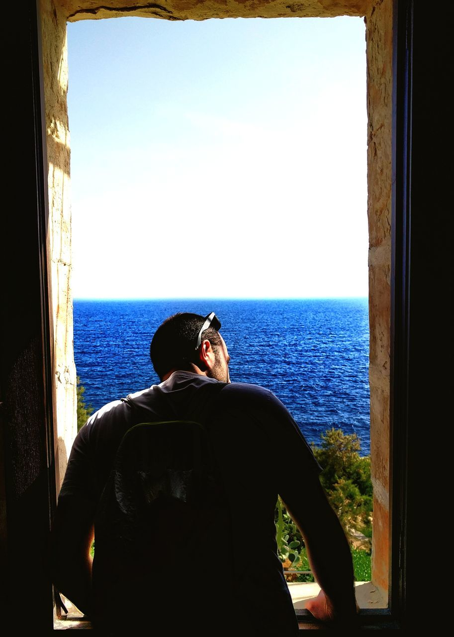 window, sea, real people, rear view, one person, looking through window, leisure activity, indoors, clear sky, day, looking at view, nature, sunlight, water, scenics, lifestyles, men, horizon over water, beauty in nature, sky, young adult