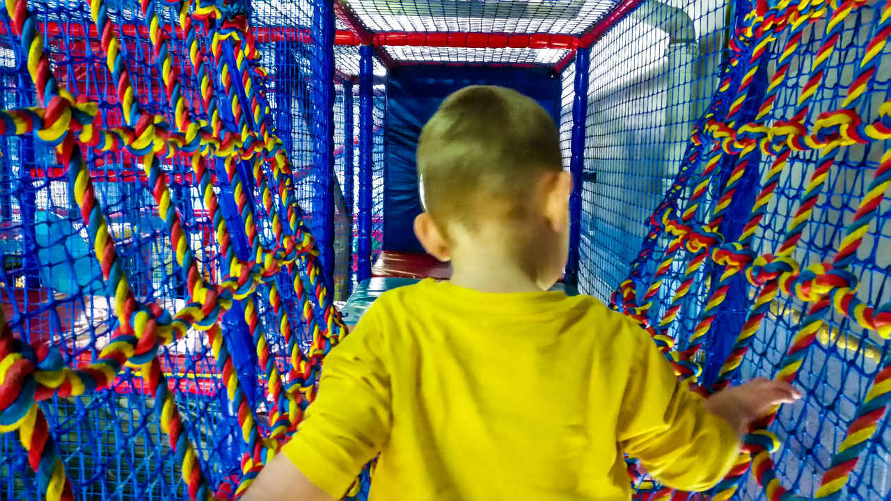 Showing Imperfection Telling Stories Differently Up Close Street Photography Child Boy Toddler  Blurred Motion Motion Blur From Behind Soft Play Ropes Multi Coloured Colourful Vibrant Net Play Area Indoor Real People Kid Childhood Playing Blonde Climbing Tee Shirt Playground