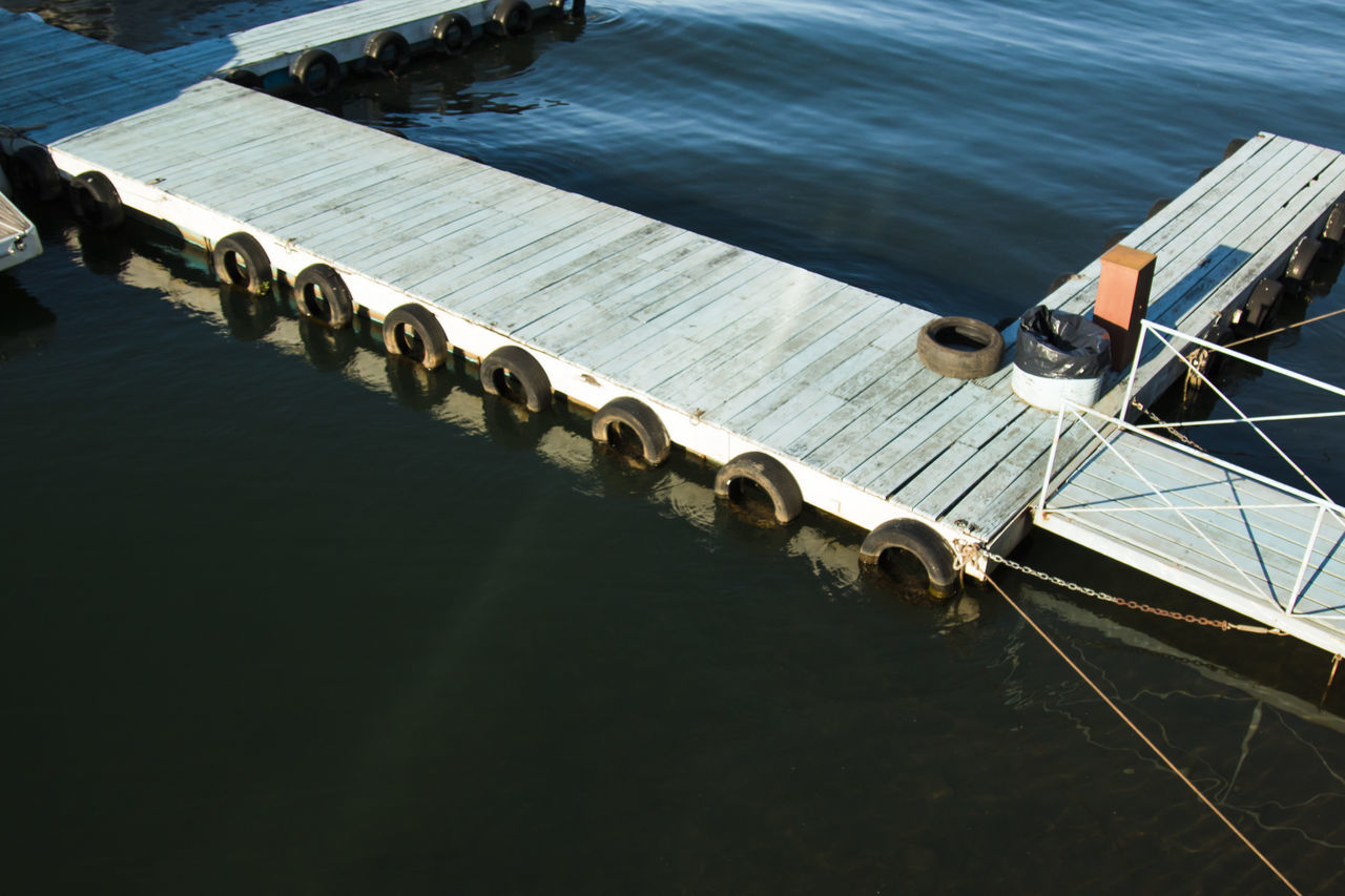 High Angle View Of Tires Hanging From Jetty In Sea