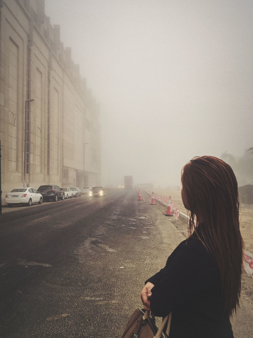 rear view, real people, car, architecture, land vehicle, transportation, one person, built structure, women, lifestyles, road, building exterior, leisure activity, outdoors, fog, day, city, sky, people