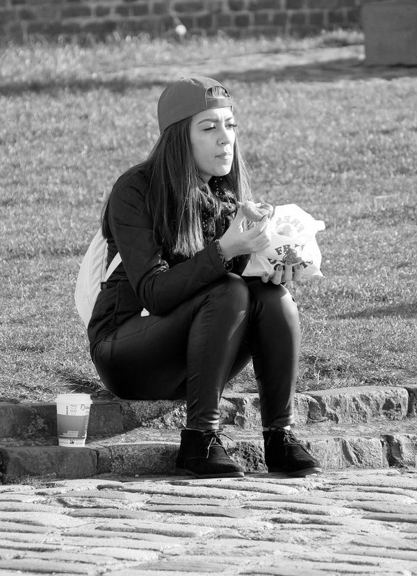 Streetphotography Streetlife Monochrome Photography Black And White Young Woman Sitting Eating Doughnut Cobbles Picsartrefugees Candid Snap A Stranger
