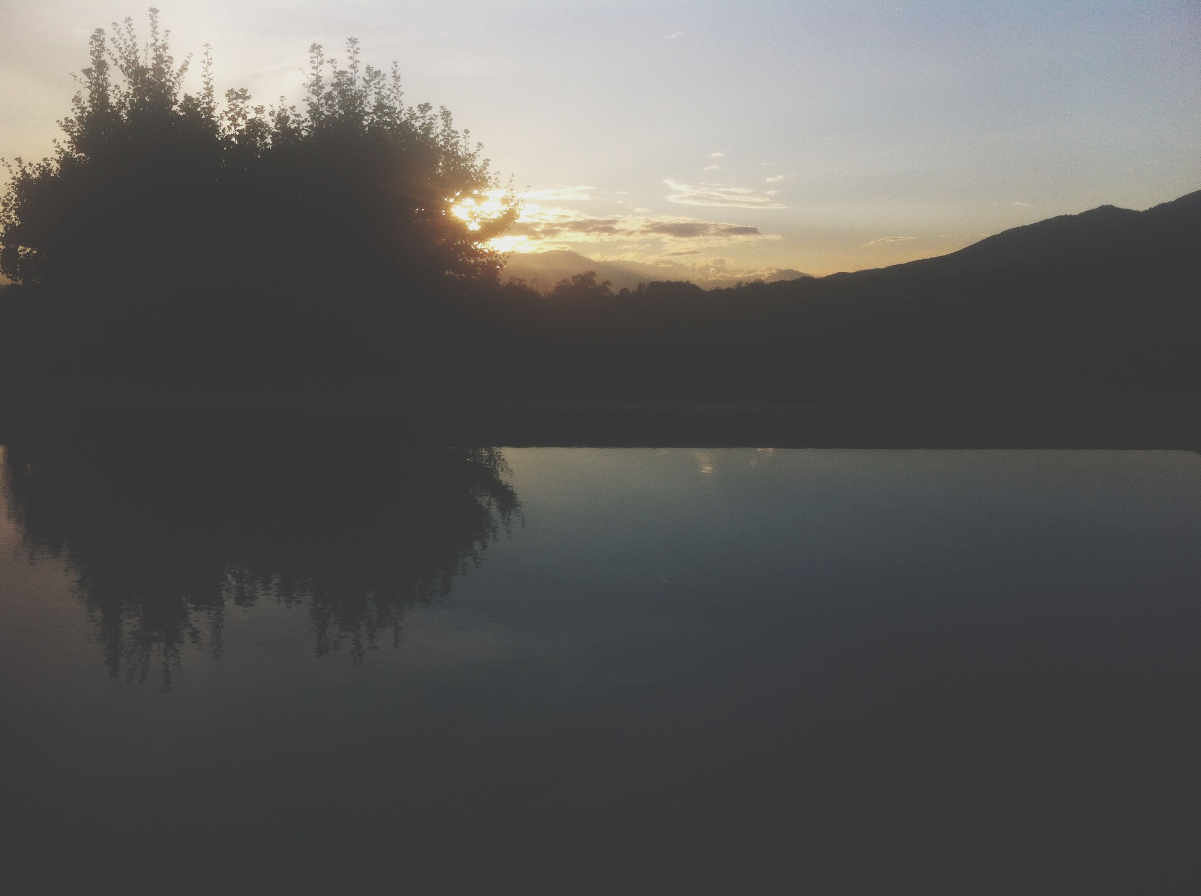 sunset, silhouette, tranquil scene, tranquility, tree, scenics, beauty in nature, water, reflection, lake, sky, nature, idyllic, sun, mountain, outdoors, no people, calm, clear sky, river