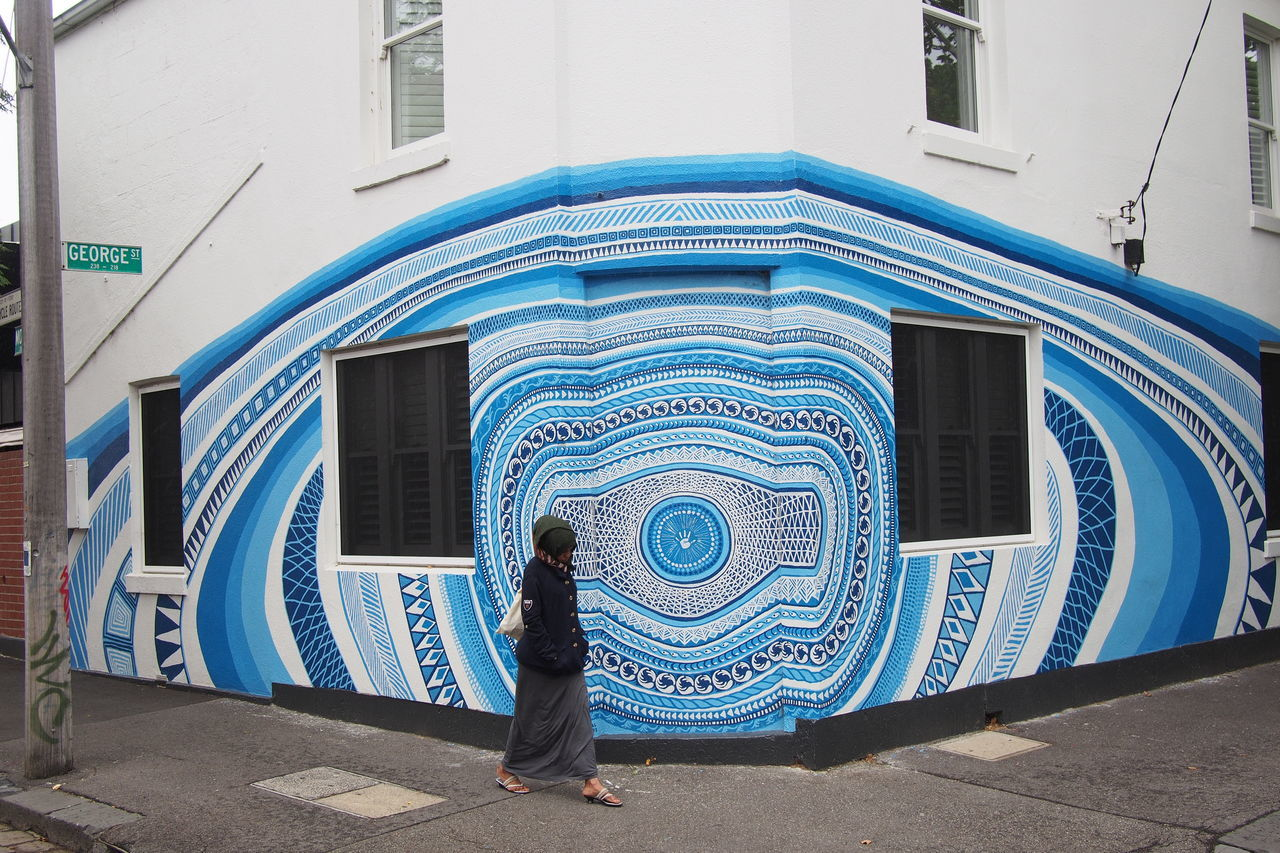 Woman Walking On Street By Building With Design