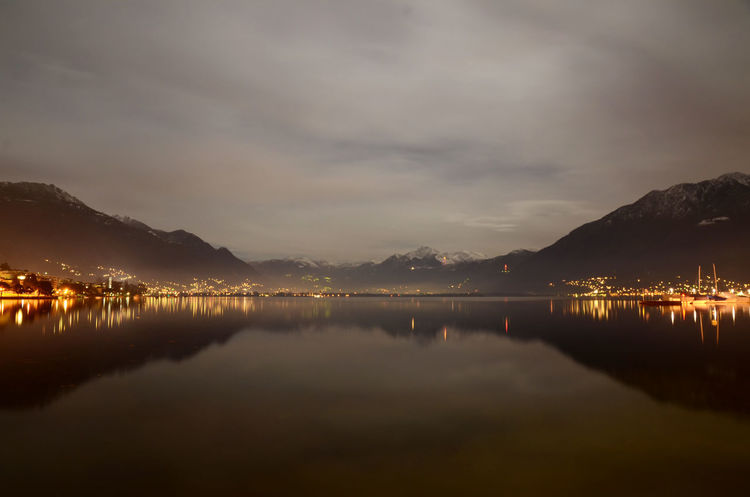 Alpine lake Maggiore at night with mountain in Ticino, Switzerland. Alpine Lake Beauty Beauty In Nature Cityscape Cloudscape Idyllic Illuminated Lake Lake Maggiore Landscape Lull Mirror Image Mountain Mountain Range Nature Night No People Outdoors Reflection Scenics Snow-capped Swiss Alps Tranquility Travel Destinations Water