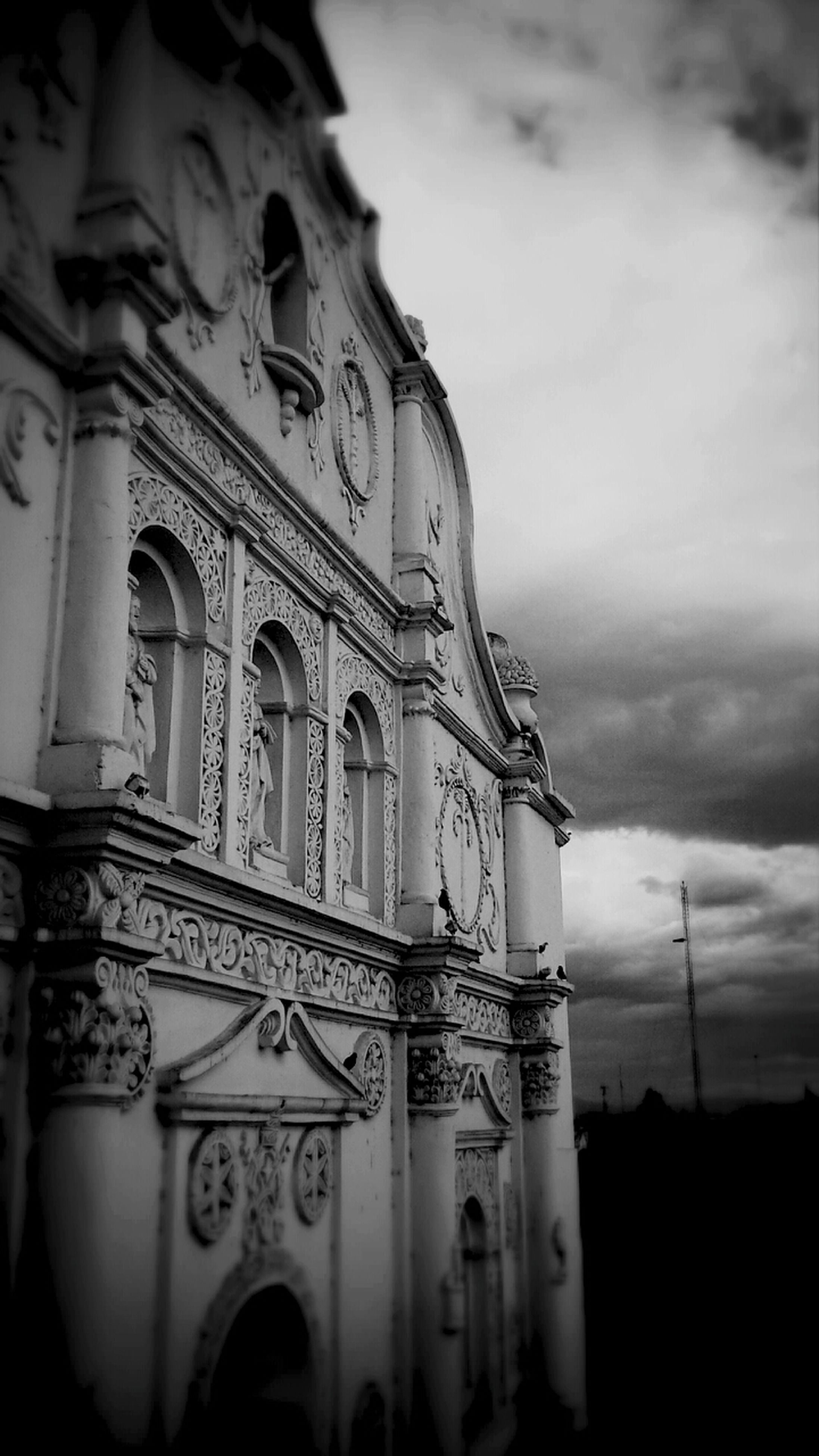 religion, spirituality, architecture, place of worship, built structure, low angle view, building exterior, history, sky, outdoors, cloud - sky, no people, travel destinations, sculpture, day