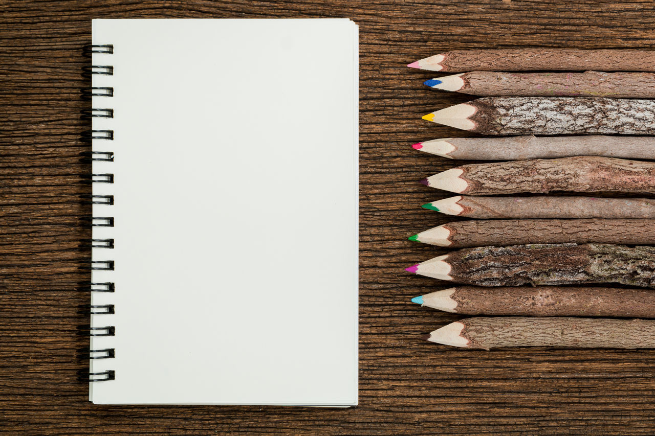 Top view of white blank empty notebook and wooden tree branch colorful pencils on wooden background. Books Business Colored Pencil Colorful Colors Drawing Education Equipment High Angle View Multi Colored Note Pad Objects Office Paper Pencil Pencils Spiral Spiral Notebook Table Trees Variation Wood Wood - Material Wooden Writing Instrument