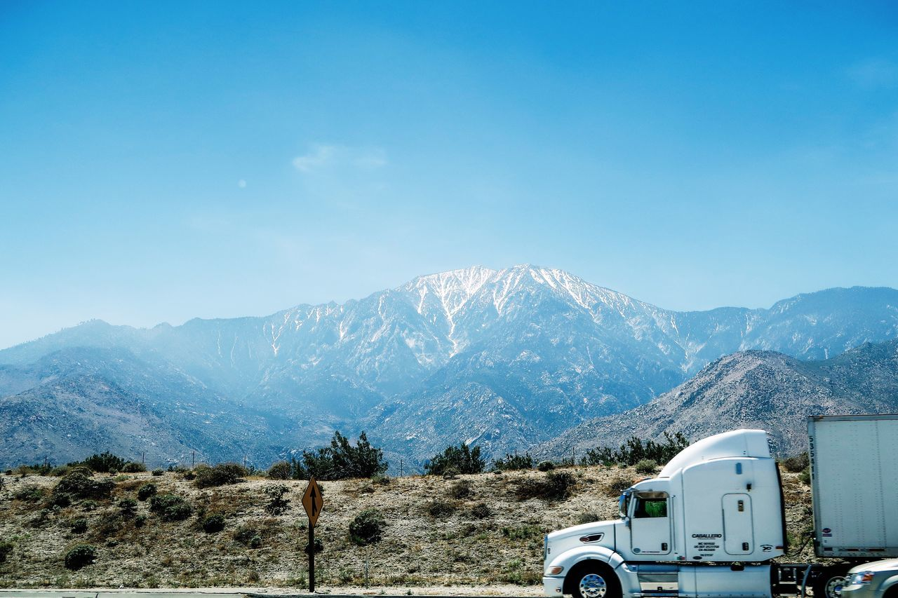 The top of mountain in the snow Beauty In Nature Blue Day Freeway Highway Landscape Logistics Mountain Mountain Range Nature Outdoors Sky Transportation Truck