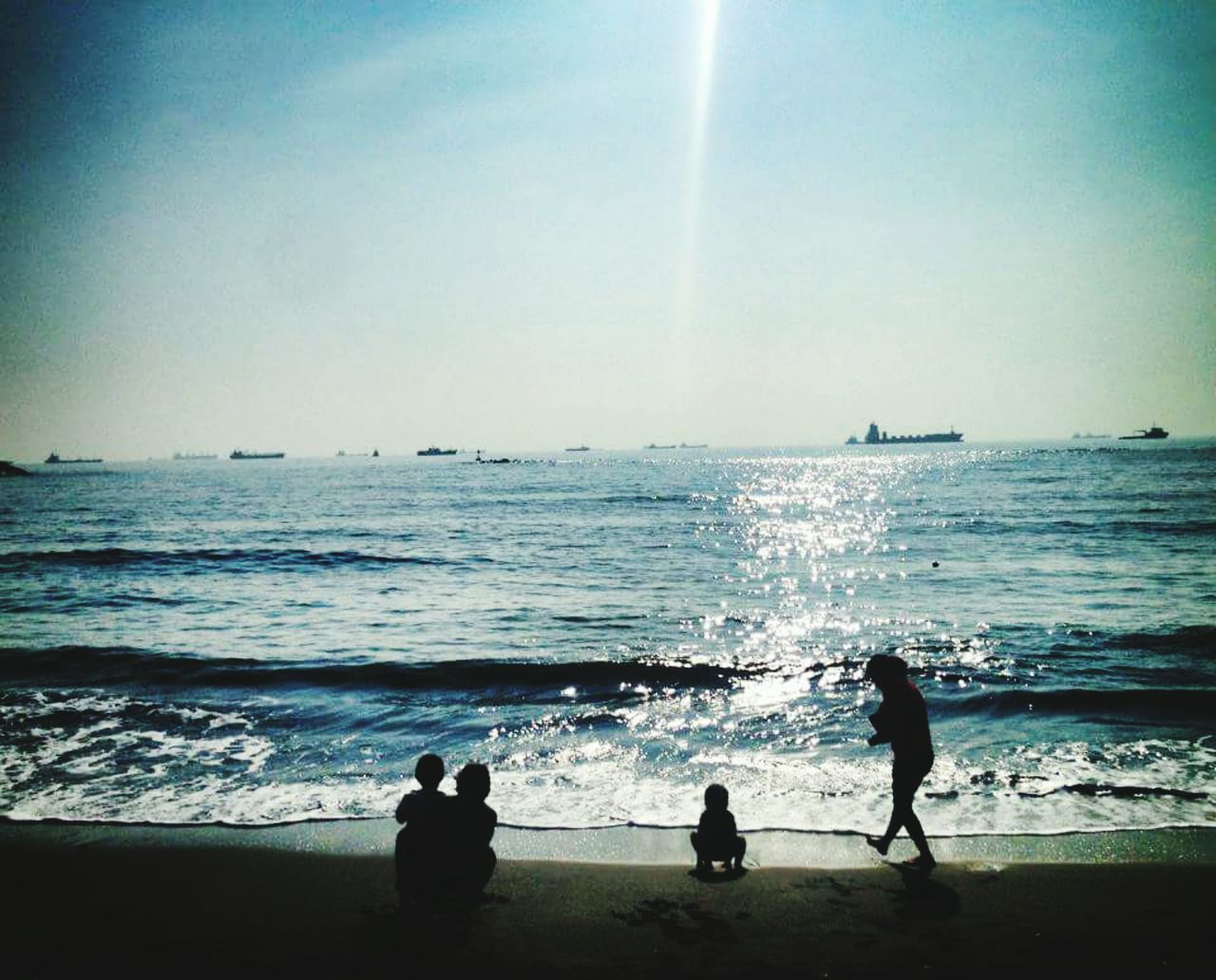 sea, real people, water, leisure activity, beach, nature, horizon over water, standing, wave, togetherness, silhouette, vacations, men, beauty in nature, lifestyles, scenics, boys, childhood, motion, outdoors, sky, son, women, day, sand, clear sky, full length, people
