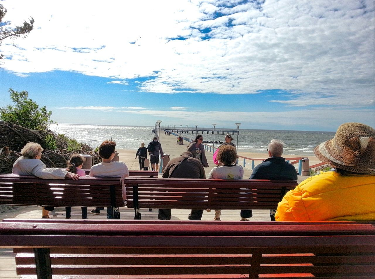 large group of people, sky, real people, men, water, railing, women, cloud - sky, sea, day, sitting, leisure activity, lifestyles, nature, outdoors, horizon over water, togetherness, group of people, adult, people