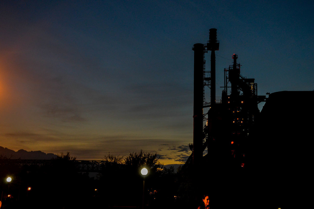 industry, silhouette, sunset, night, no people, built structure, architecture, outdoors, sky, illuminated, factory, oil industry, fuel and power generation, smoke stack, building exterior, tree, nature, drilling rig