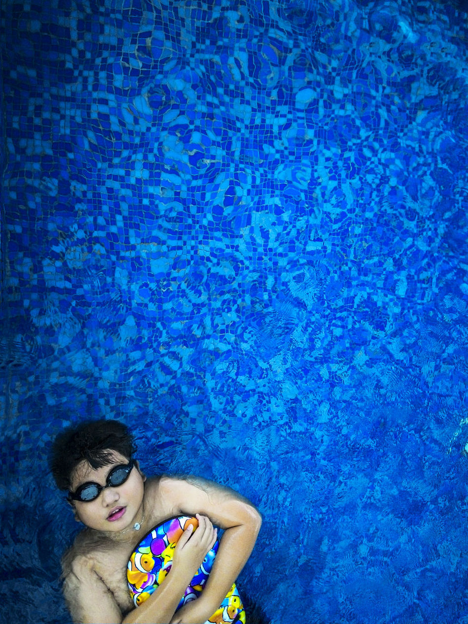 Top view of tween boy swimmer floating in outdoor swimming pool 12 Years Old A Bird's Eye View Blue Water Day Directly Above East Asian Floating On Water Healthy Lifestyle Kid Leisure Activity Male Natural Light Outdoors People Swimmer Swimming Swimming Pool Top View Tween Vertical Wellbeing Wellness The Color Of Sport