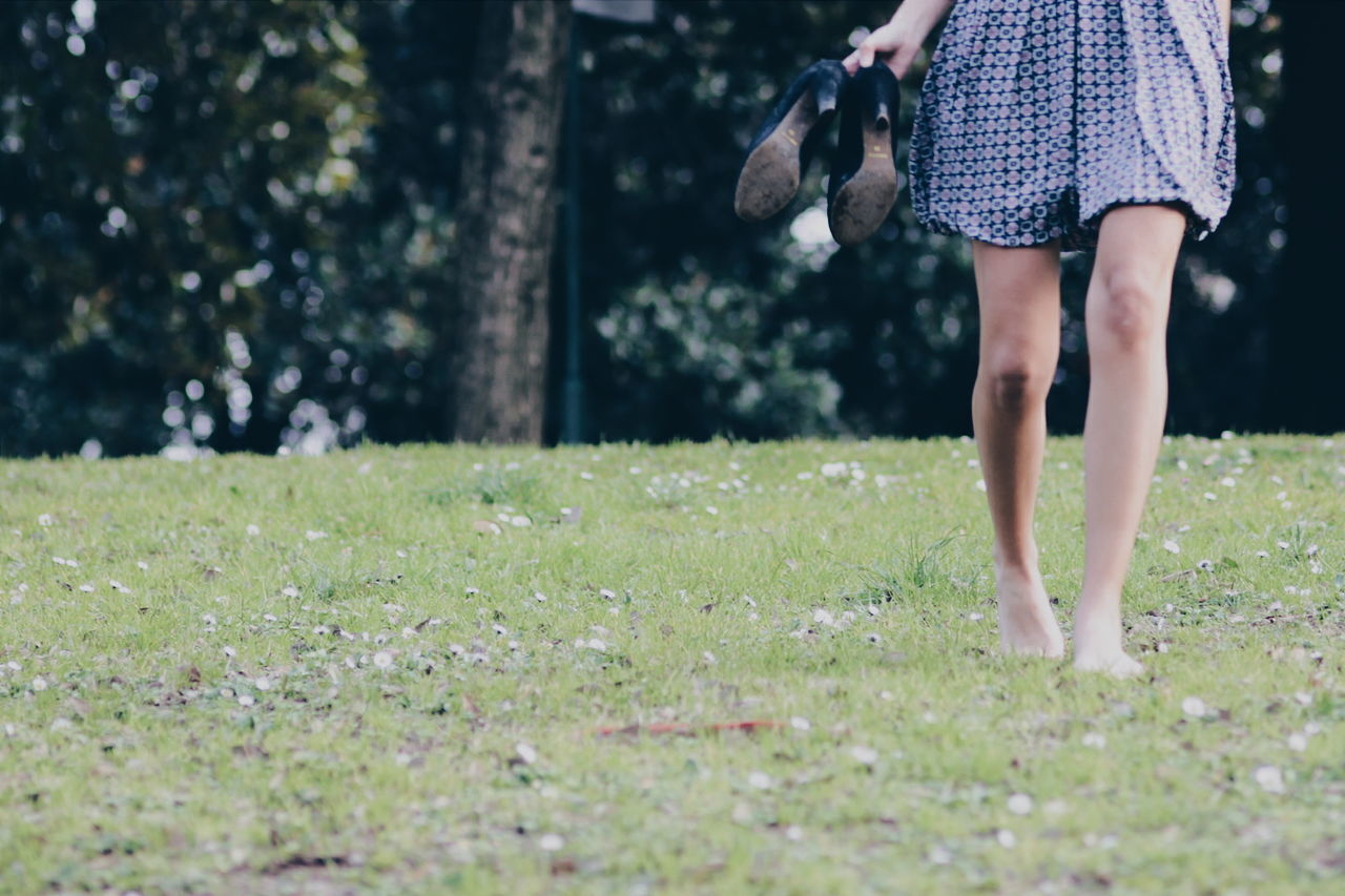 Low Section Of Woman Holding Shoes While Standing At Park