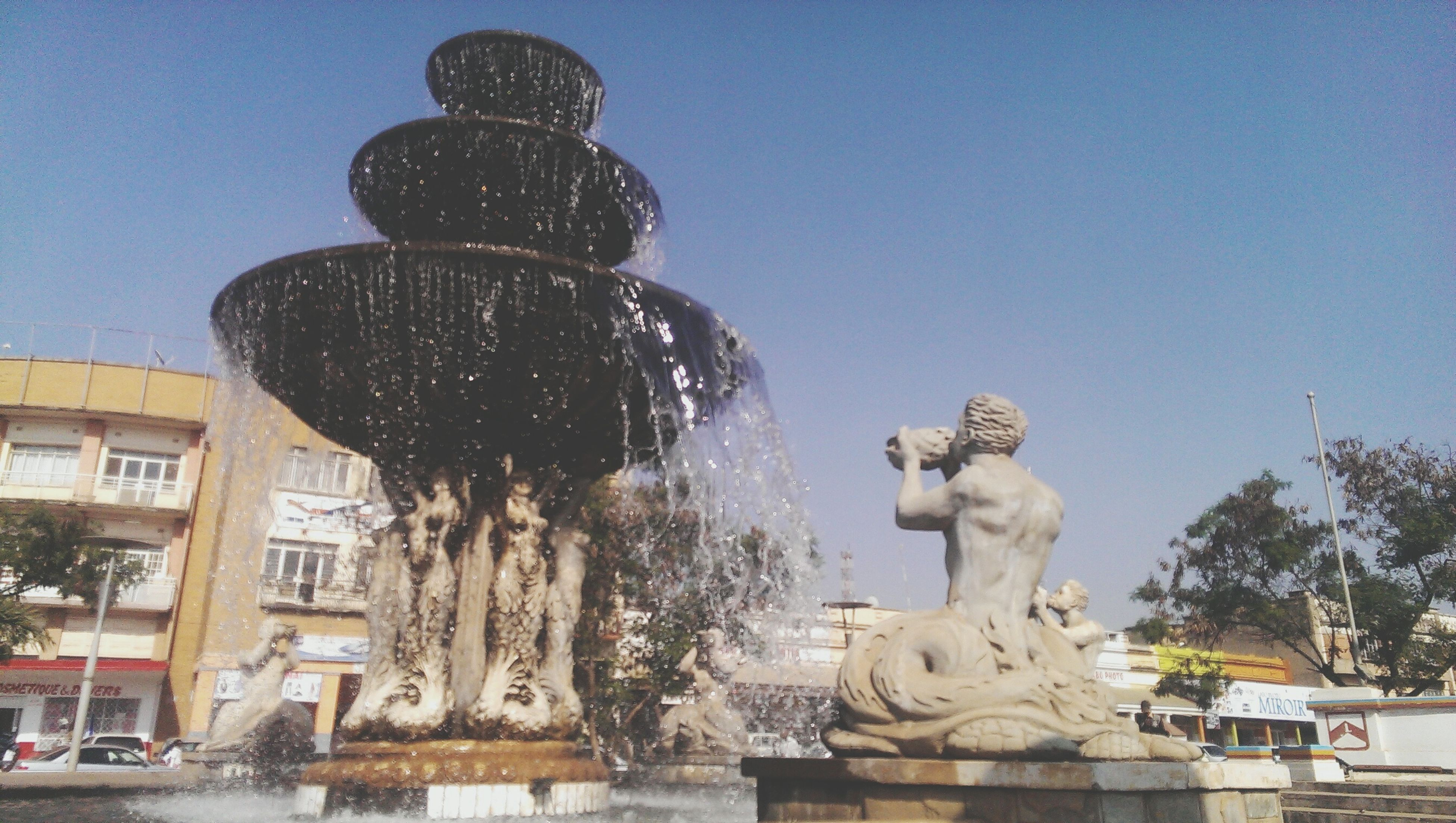 statue, sculpture, human representation, art and craft, art, creativity, animal representation, architecture, built structure, building exterior, clear sky, low angle view, fountain, city, travel destinations, craft, famous place, tree