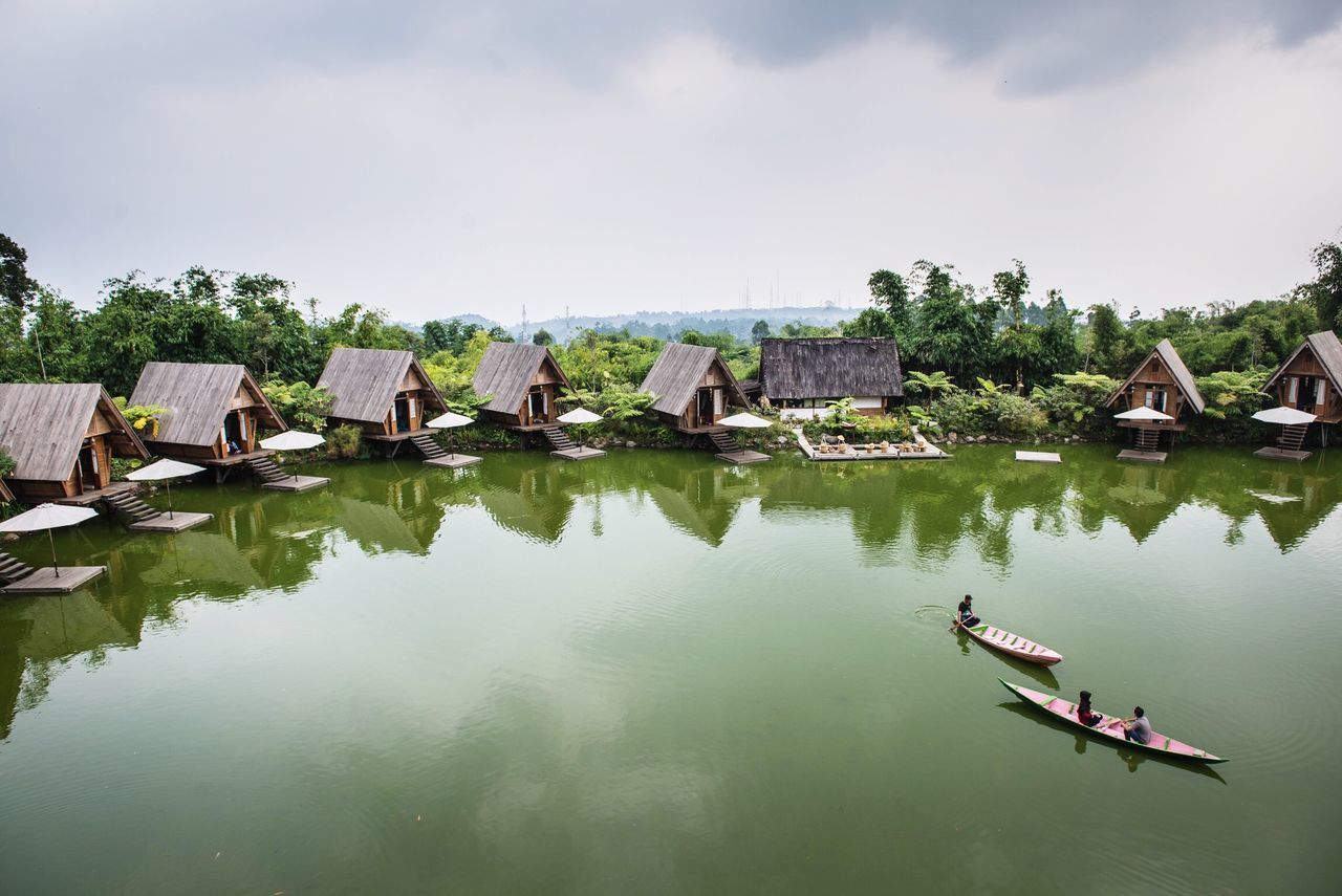 Scenic View Of Lake By Houses Against Cloudy Sky
