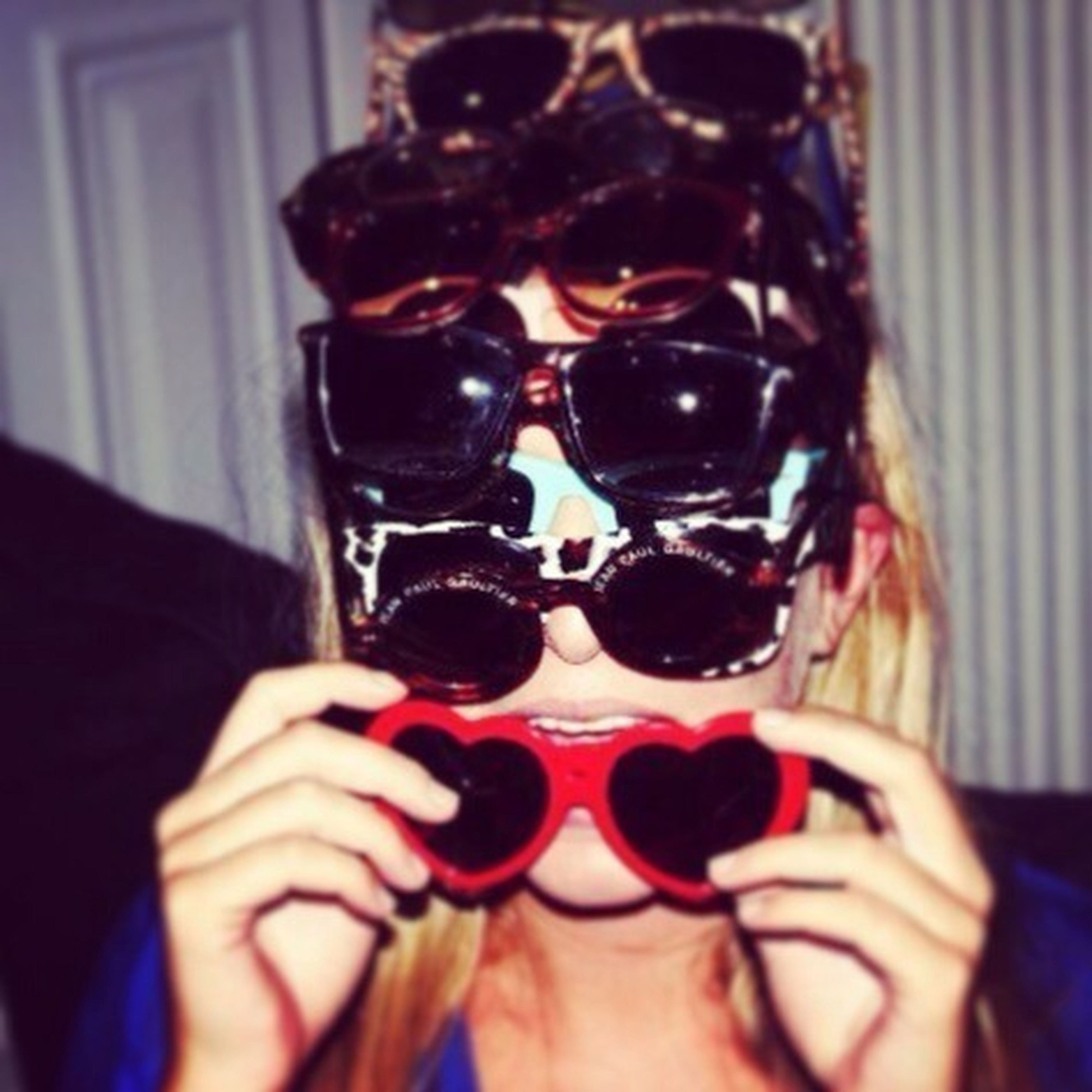 lifestyles, leisure activity, person, holding, indoors, young adult, headshot, part of, front view, looking at camera, close-up, portrait, sunglasses, young women, human finger