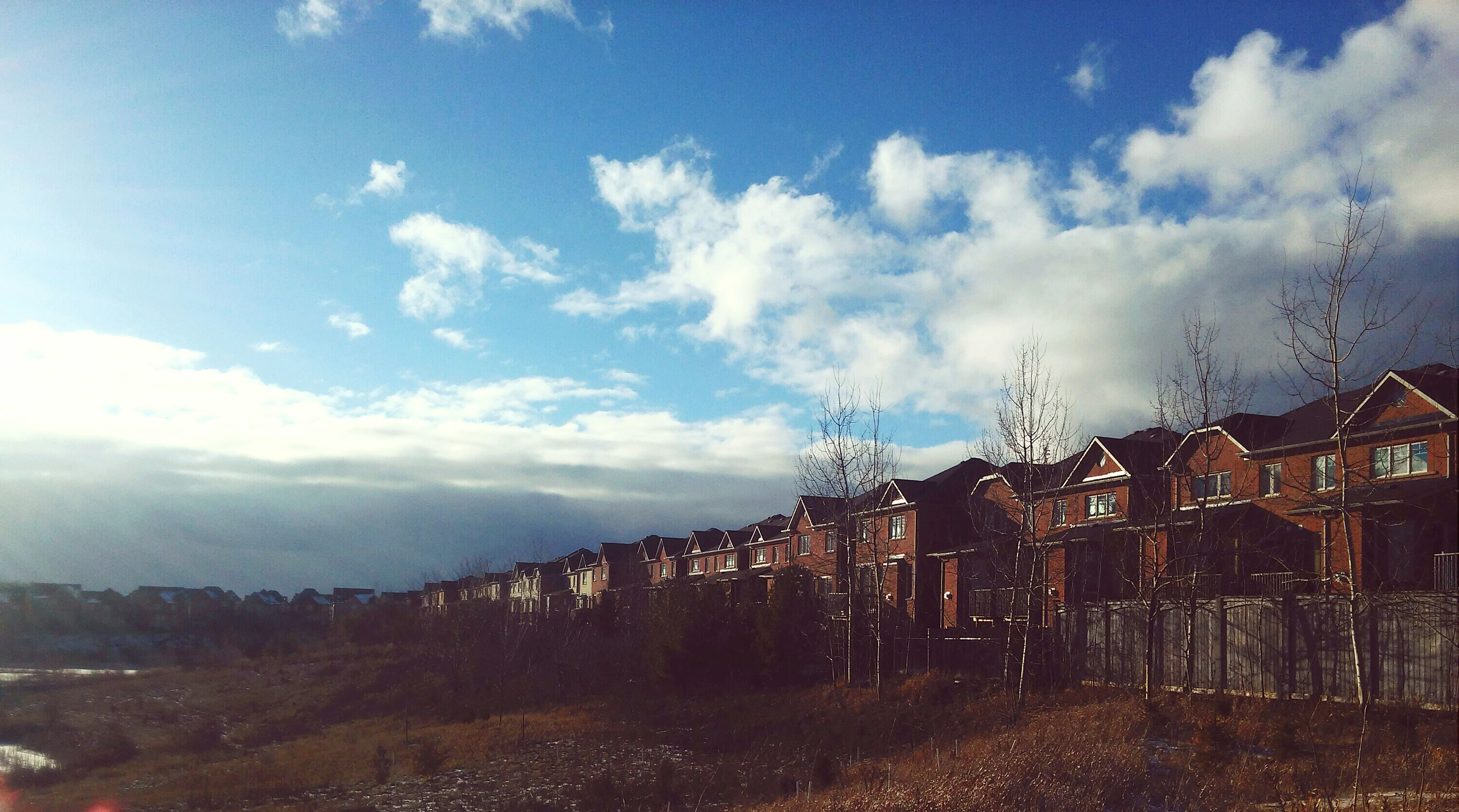 sky, built structure, architecture, building exterior, cloud - sky, house, tree, the way forward, cloud, landscape, field, residential structure, nature, road, cloudy, dirt road, day, fence, tranquility, outdoors