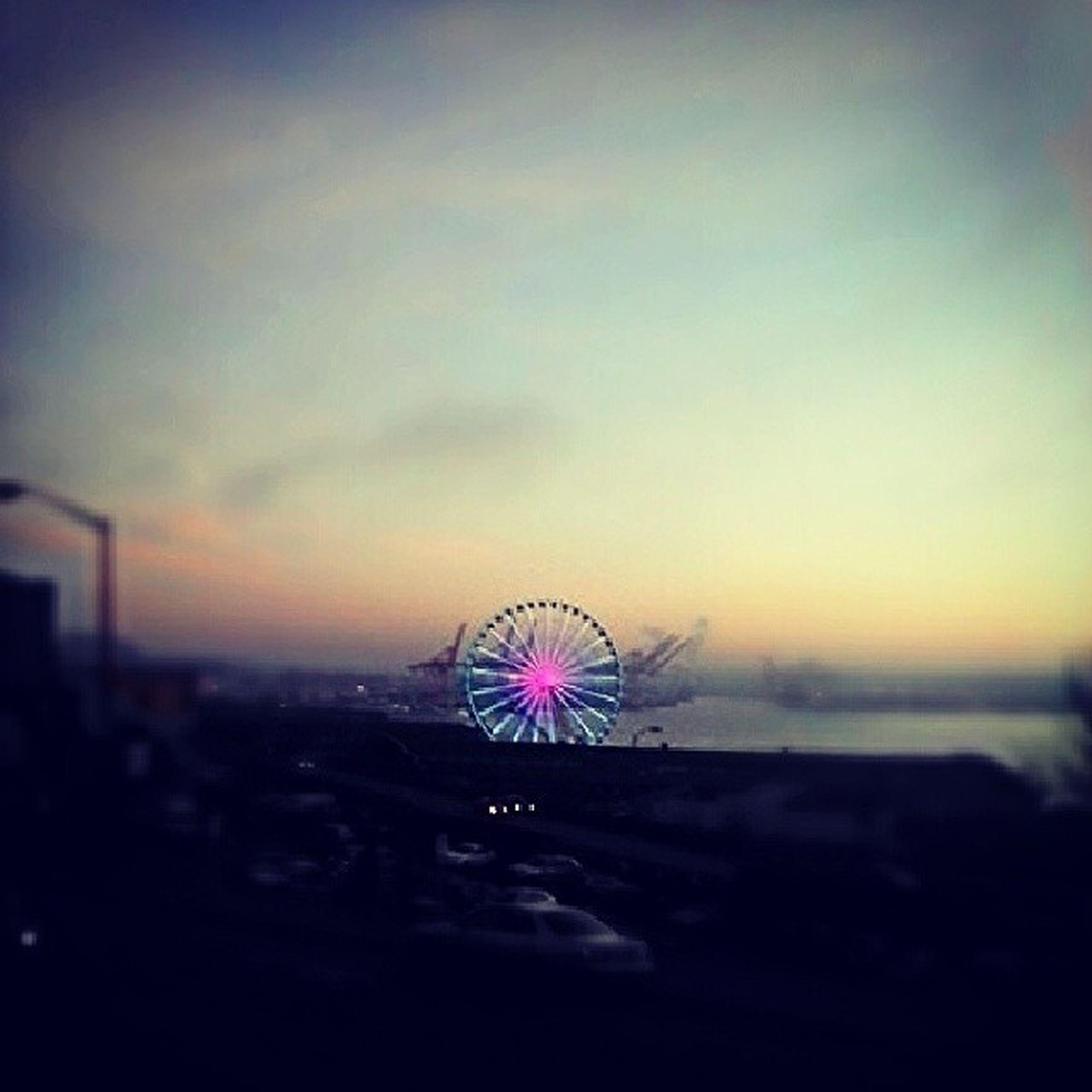 illuminated, ferris wheel, sky, arts culture and entertainment, night, amusement park ride, amusement park, multi colored, dusk, sunset, cloud - sky, outdoors, firework display, silhouette, architecture, no people, built structure, city, motion, long exposure