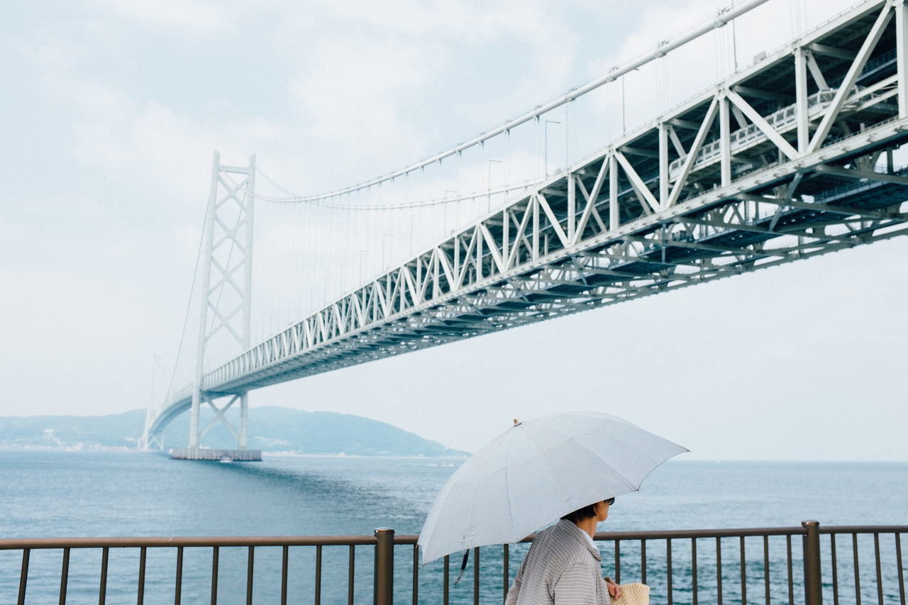 architecture, sky, engineering, bridge - man made structure, built structure, outdoors, connection, day, water, one person, suspension bridge, real people, people
