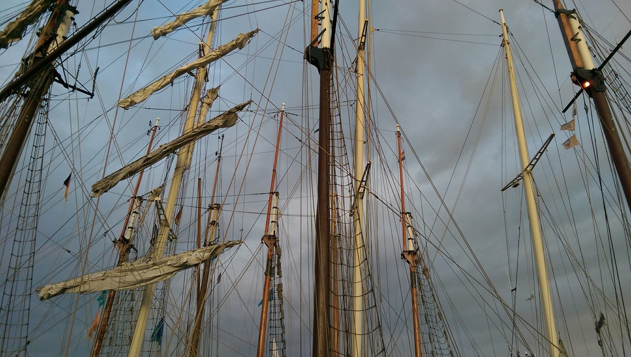 Low Angle View Of Masts Against Cloudy Sky