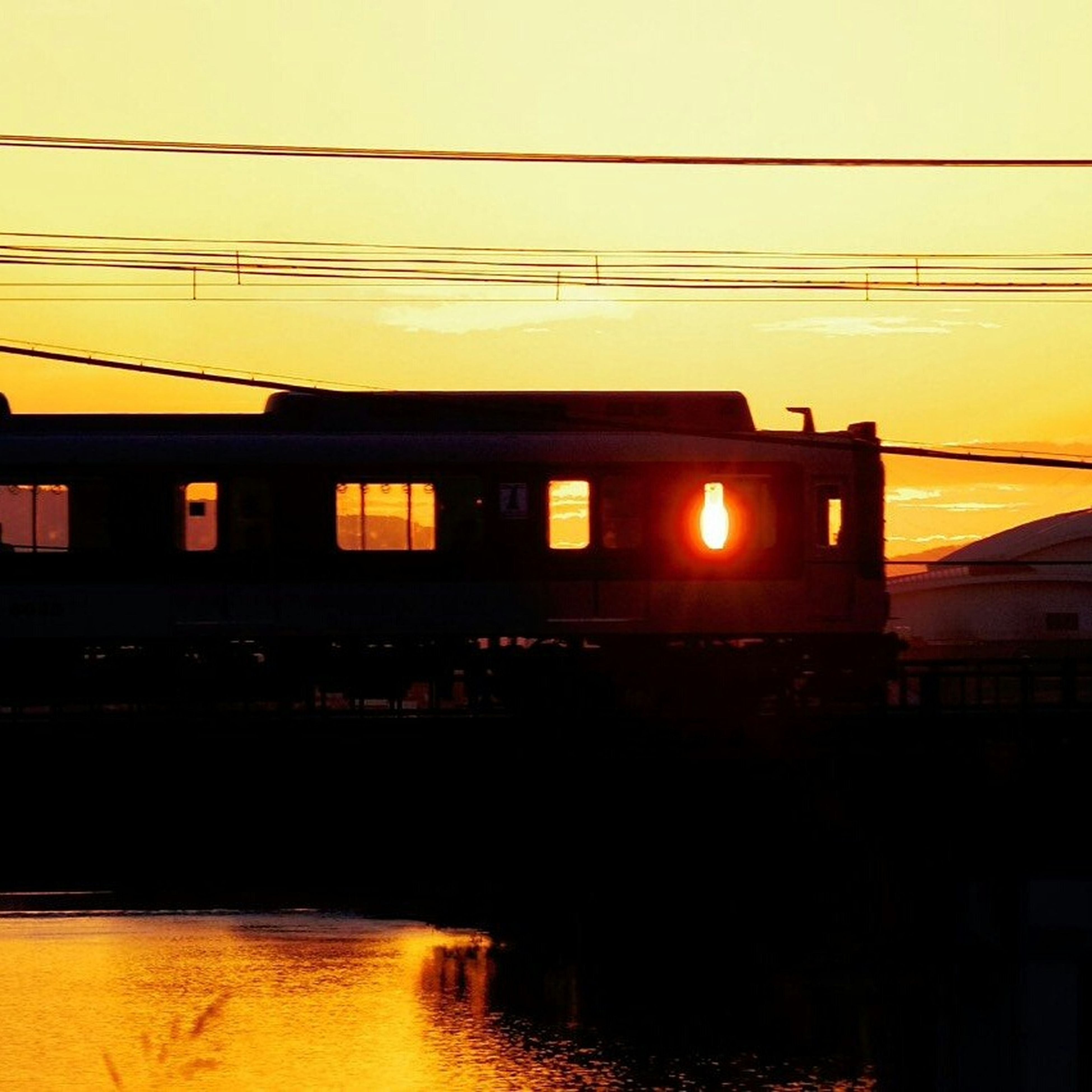 sunset, built structure, architecture, building exterior, silhouette, power line, orange color, connection, sky, cable, electricity pylon, building, electricity, illuminated, no people, reflection, outdoors, city, bridge - man made structure, low angle view