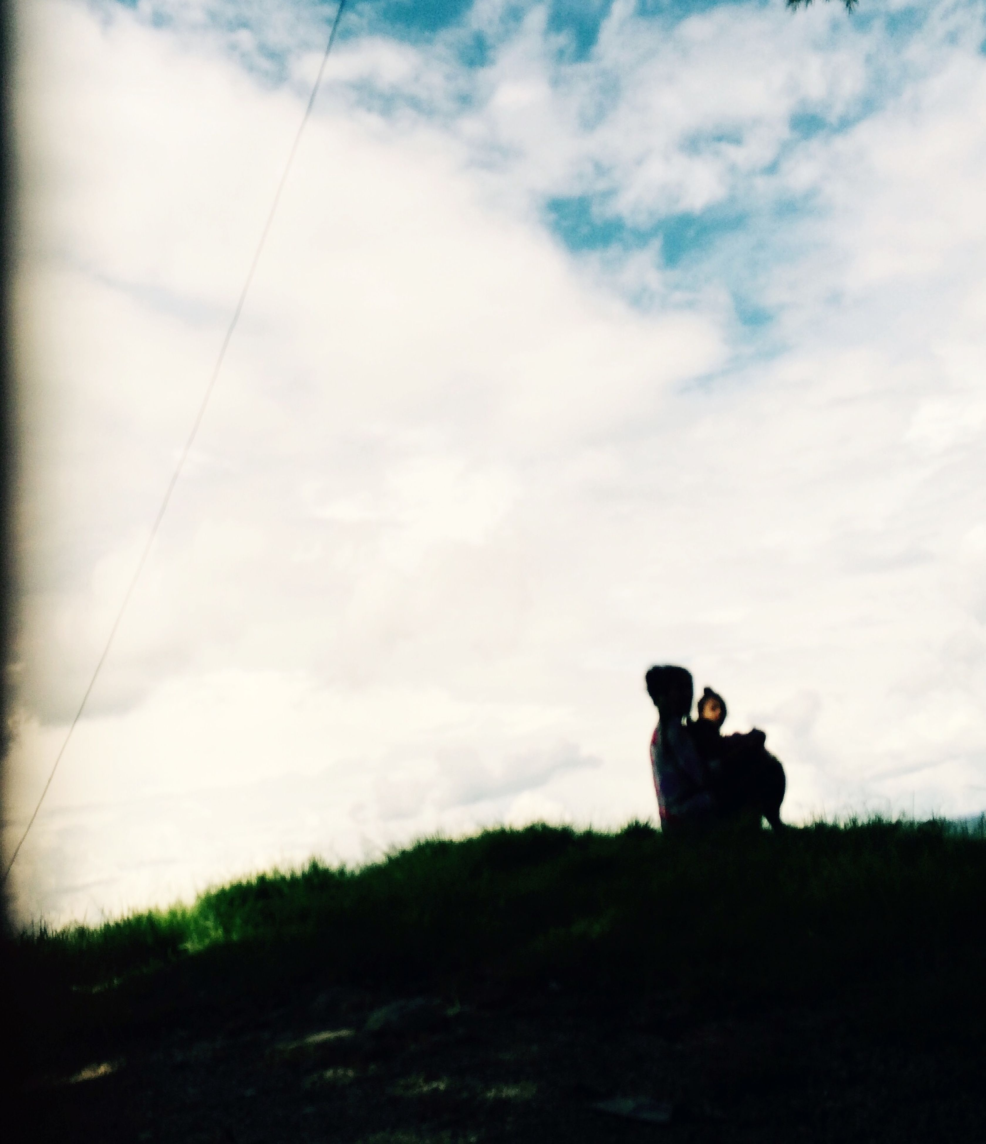 sky, lifestyles, leisure activity, men, cloud - sky, sitting, field, rear view, standing, technology, photographing, cloud, landscape, three quarter length, full length, cloudy, casual clothing, photography themes