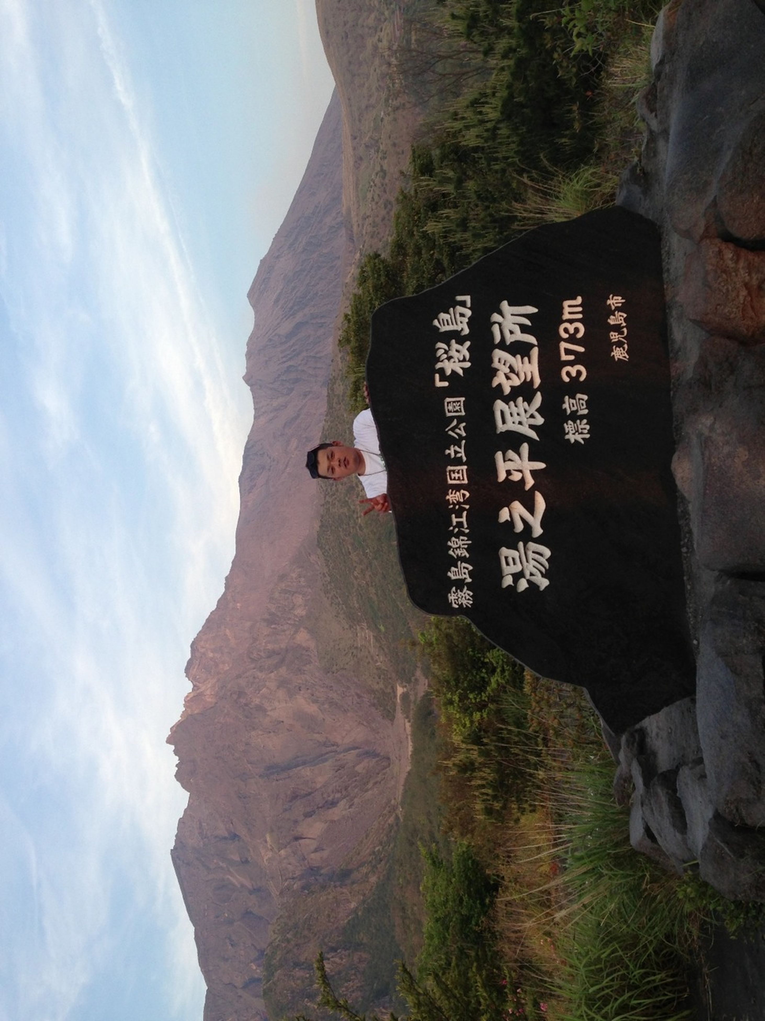 text, mountain, western script, communication, sky, rock - object, guidance, rock formation, sign, cliff, nature, information sign, landscape, day, leisure activity, architecture, travel destinations, men