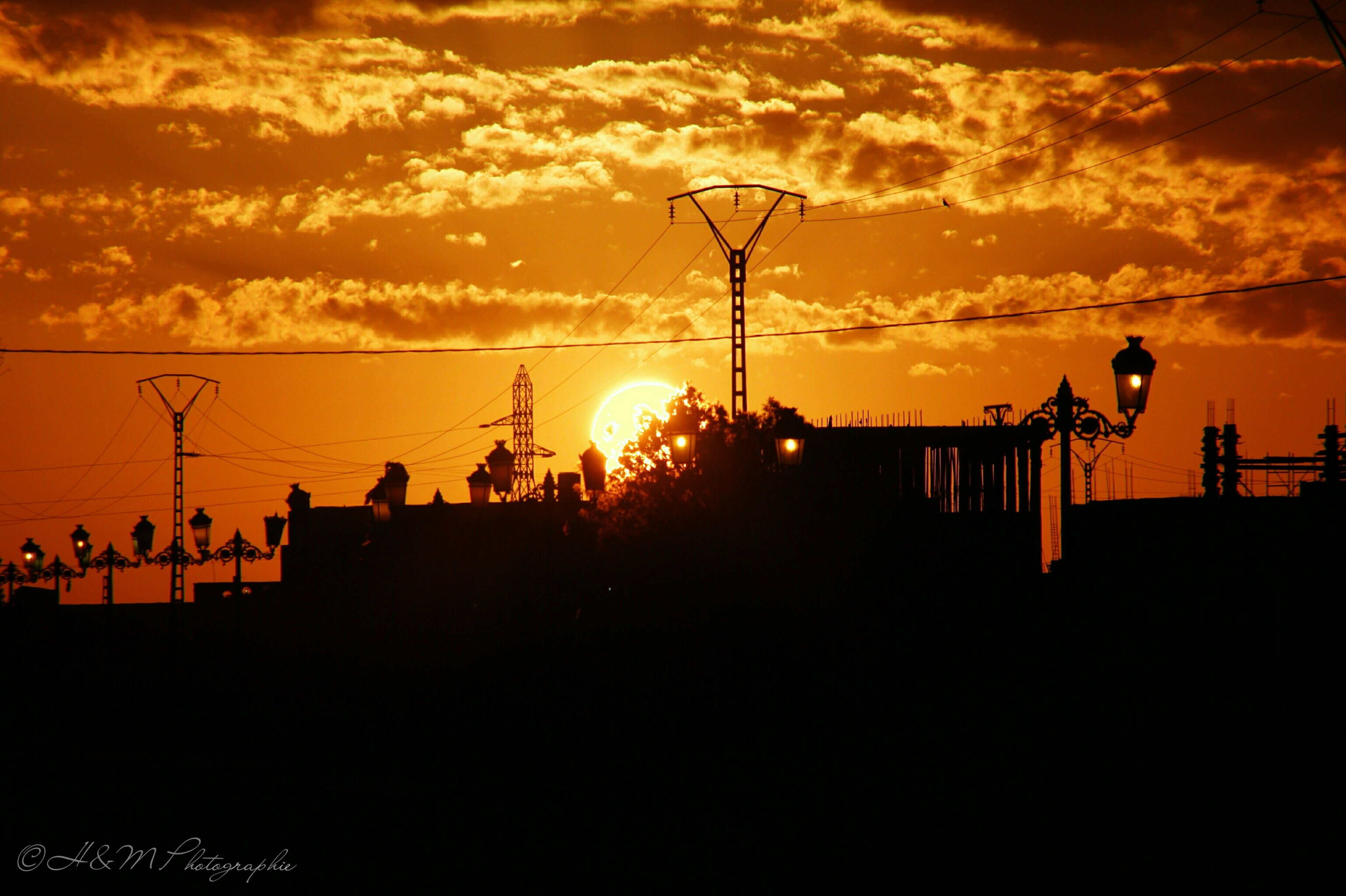 sunset, silhouette, orange color, sky, sun, power line, electricity pylon, electricity, cloud - sky, street light, fuel and power generation, building exterior, built structure, beauty in nature, low angle view, nature, technology, architecture, scenics, power supply