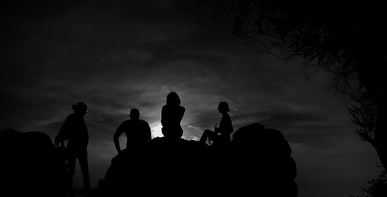 Silhouette Of People Sitting On Boulder Against Sky