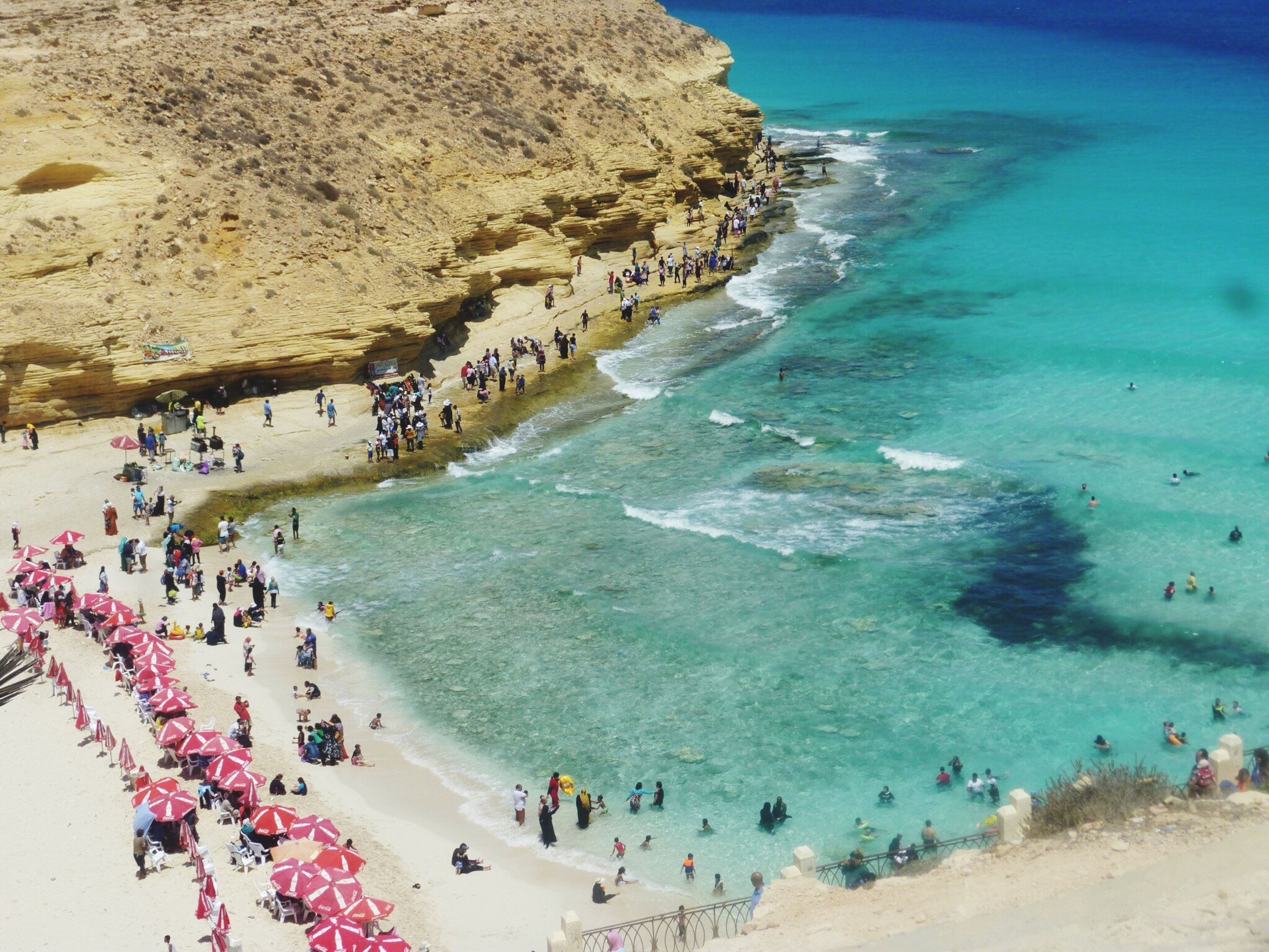 sea, beach, large group of people, water, high angle view, wave, sand, shore, coastline, leisure activity, real people, enjoyment, horizon over water, beauty in nature, outdoors, scenics, fun, day, vacations, nature, sky, men, crowd, people