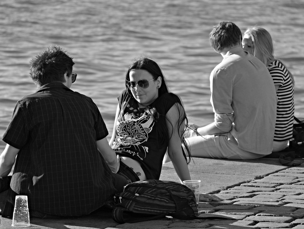 sitting, togetherness, leisure activity, real people, casual clothing, women, men, bonding, day, outdoors, young women, lifestyles, water, two people, full length, young adult, friendship, nature, adult, people