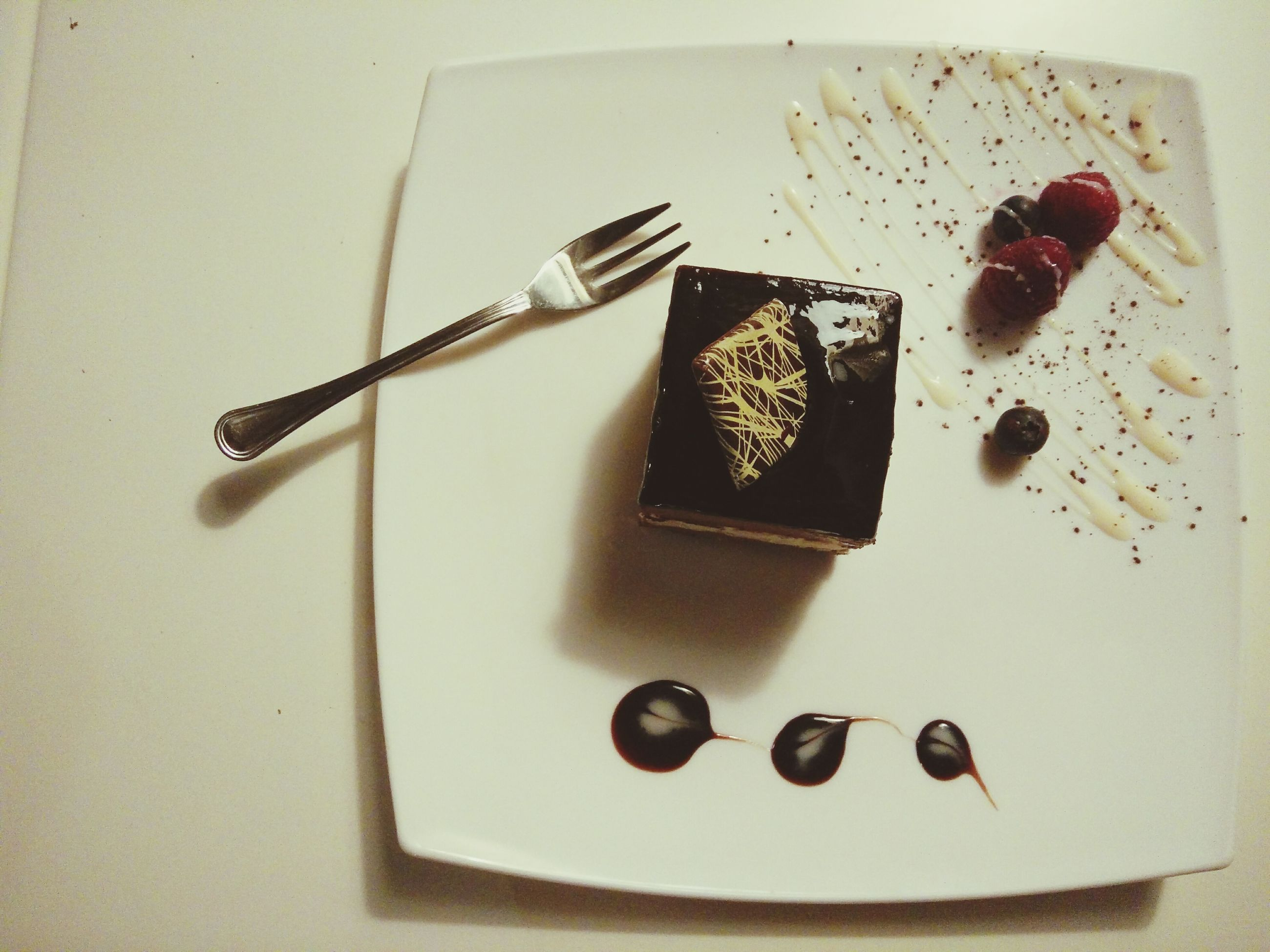 indoors, still life, table, food and drink, high angle view, close-up, food, sweet food, no people, variation, hanging, cake, plate, wall - building feature, fork, chocolate, decoration, selective focus, shadow, freshness