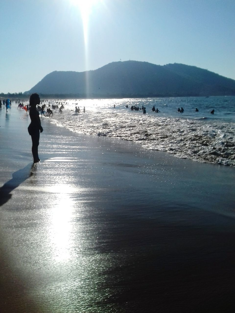 water, beach, sunlight, sea, real people, nature, scenics, beauty in nature, mountain, one person, full length, outdoors, silhouette, day, sky, vacations, standing, clear sky, people