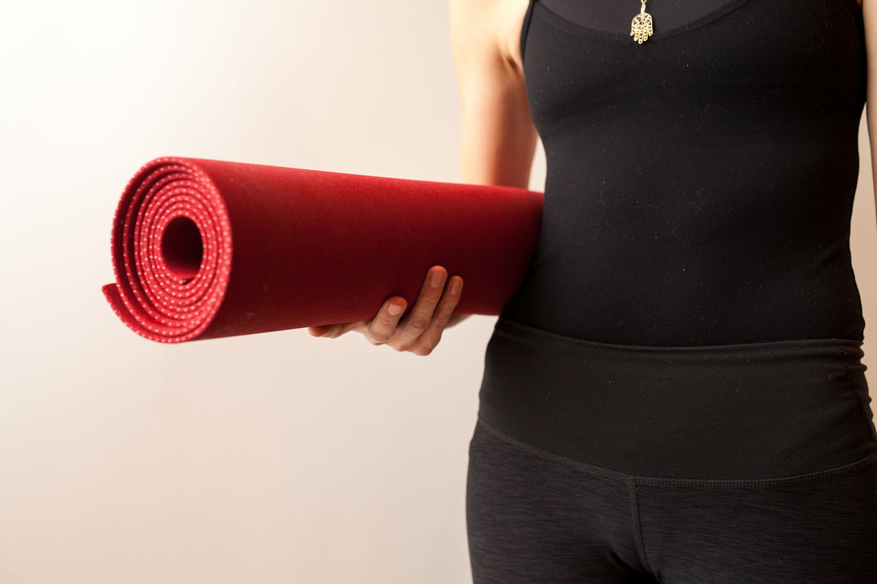 Midsection Of Woman Holding Exercise Mat Against Wall