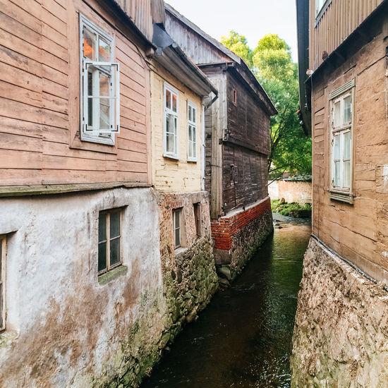 Aleksupite river winding through town, Kuldiga. Latvia Architecture Bad Condition Building Building Exterior Built Structure Day Deterioration Exterior Façade House Kuldiga Latvia Obsolete Old Outdoors Residential Building Residential Structure River Roof Stream Town Village Window Wooden