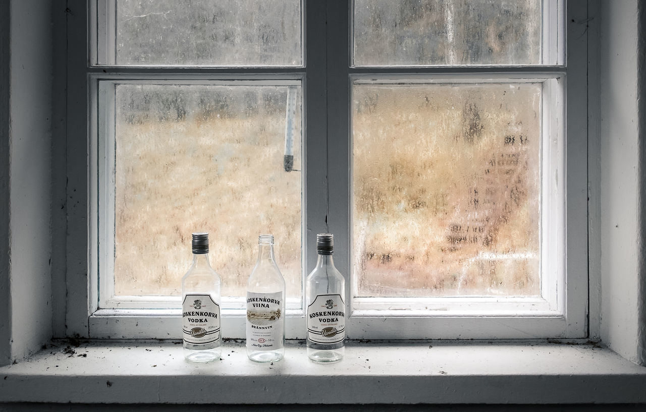 Tree alcohol bottles in abandoned house. Abandoned Places Alcohol Bottles Alcoholism Darkness And Light Day Depressed Dirty Droplets Foggy Glass - Material Gloomy Weather Indoors  Messy No People Old Window Window Ledge Worn